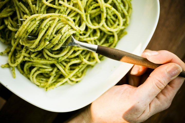 A young woman enjoys a bowl of organic pesto pasta in Seattle WA.