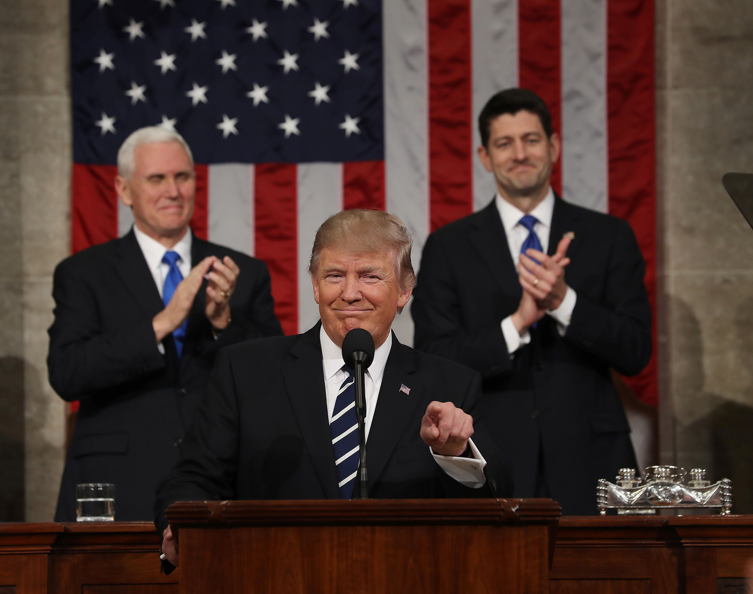 US Vice President Mike Pence (L) and Speaker of the House Paul Ryan (R) applaud as US President Donald J. Trump (C) arrives to deliver his first address to a joint session of Congress from the floor of the House of Representatives in Washington, DC, USA, on February 28, 2017.