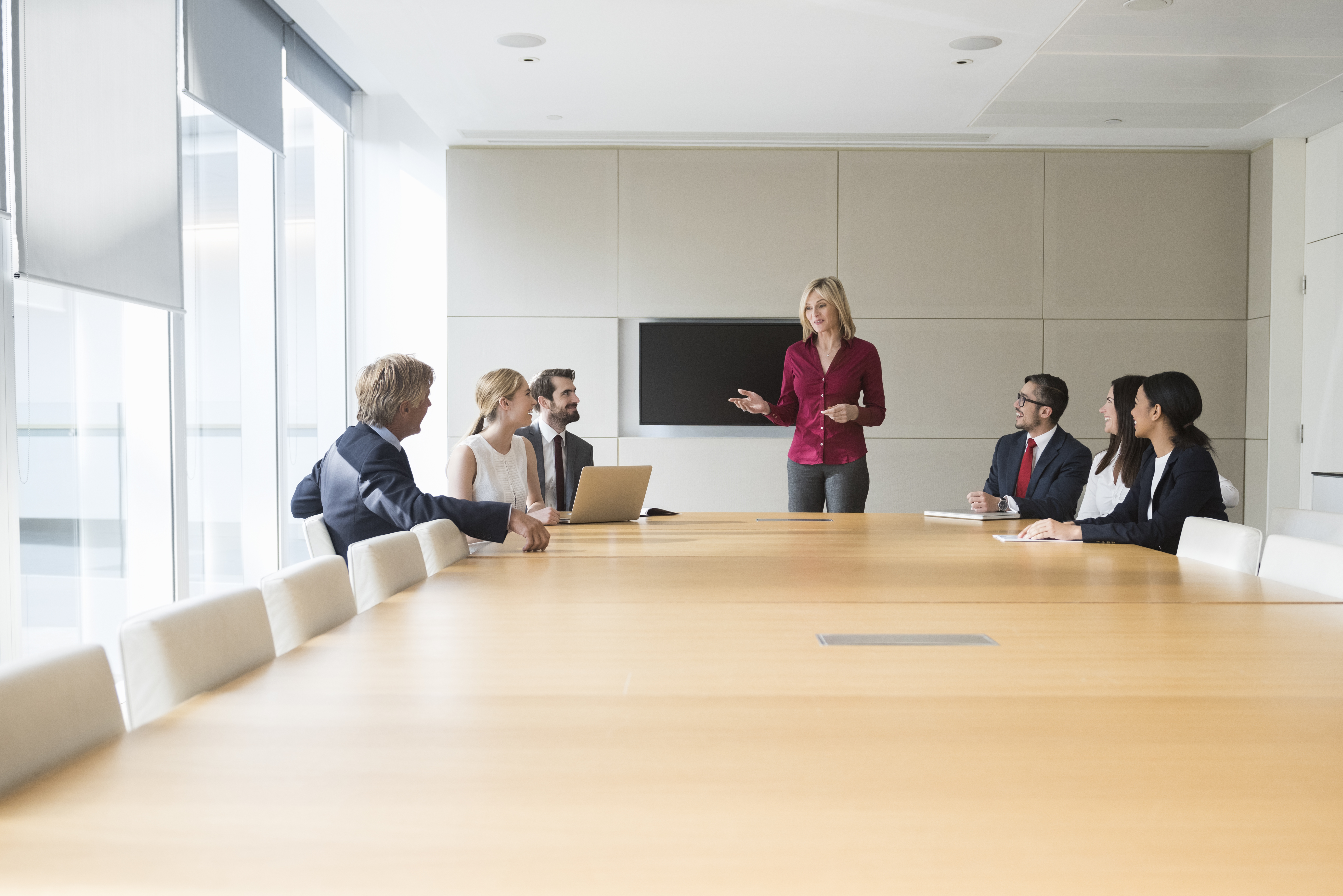 A photo of businesswoman giving presentation to colleagues at conference table. Professionals are in formals. Business people are in board room. Concentrated associates listening to presentation, in a brightly lit modern office.