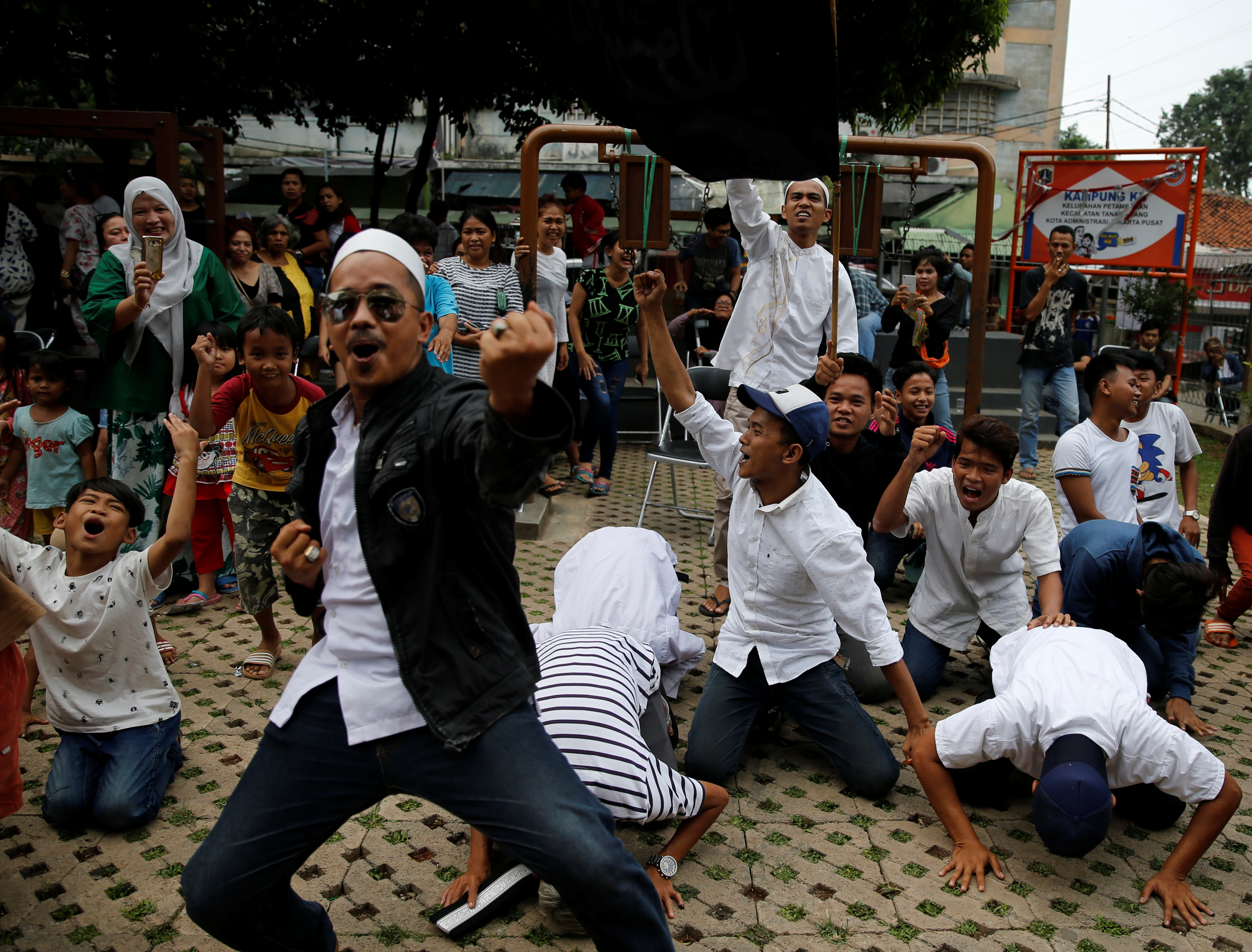 Supporters of Anies Baswedan, at a polling station in Jakarta, on April 19, 2017, react as they hear that he leads the vote count in an election to become the city's governor