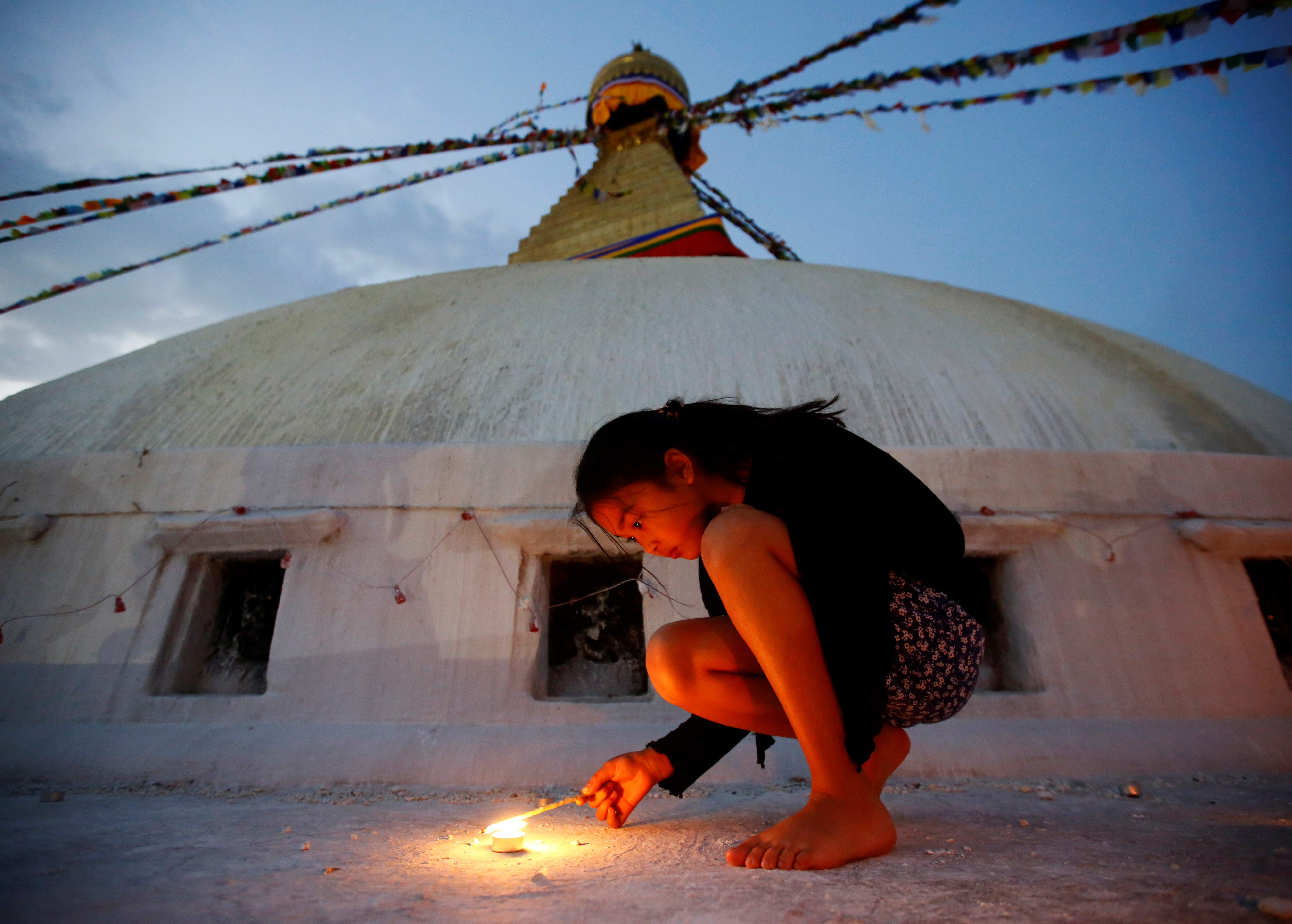 A girl lights a candle as she marks the anniversary of 2015 Nepal earthquake, at Boudhanath stupa in Kathmandu on April 25, 2017
