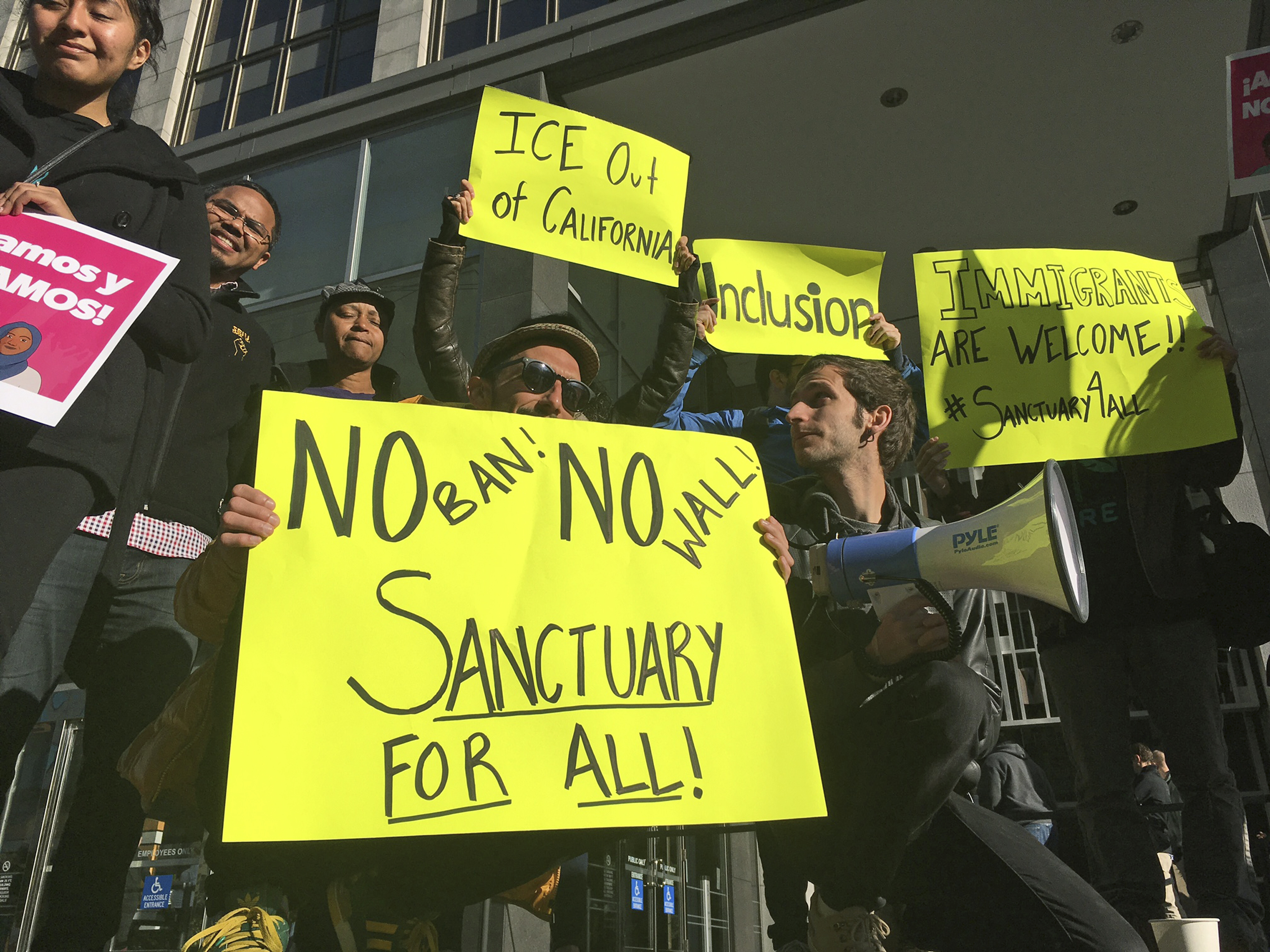 Protesters hold up signs outside a courthouse where a federal judge will hear arguments in the first lawsuit challenging President Donald Trump's executive order to withhold funding from communities that limit cooperation with immigration authorities on April 14, 2017, in San Francisco.
