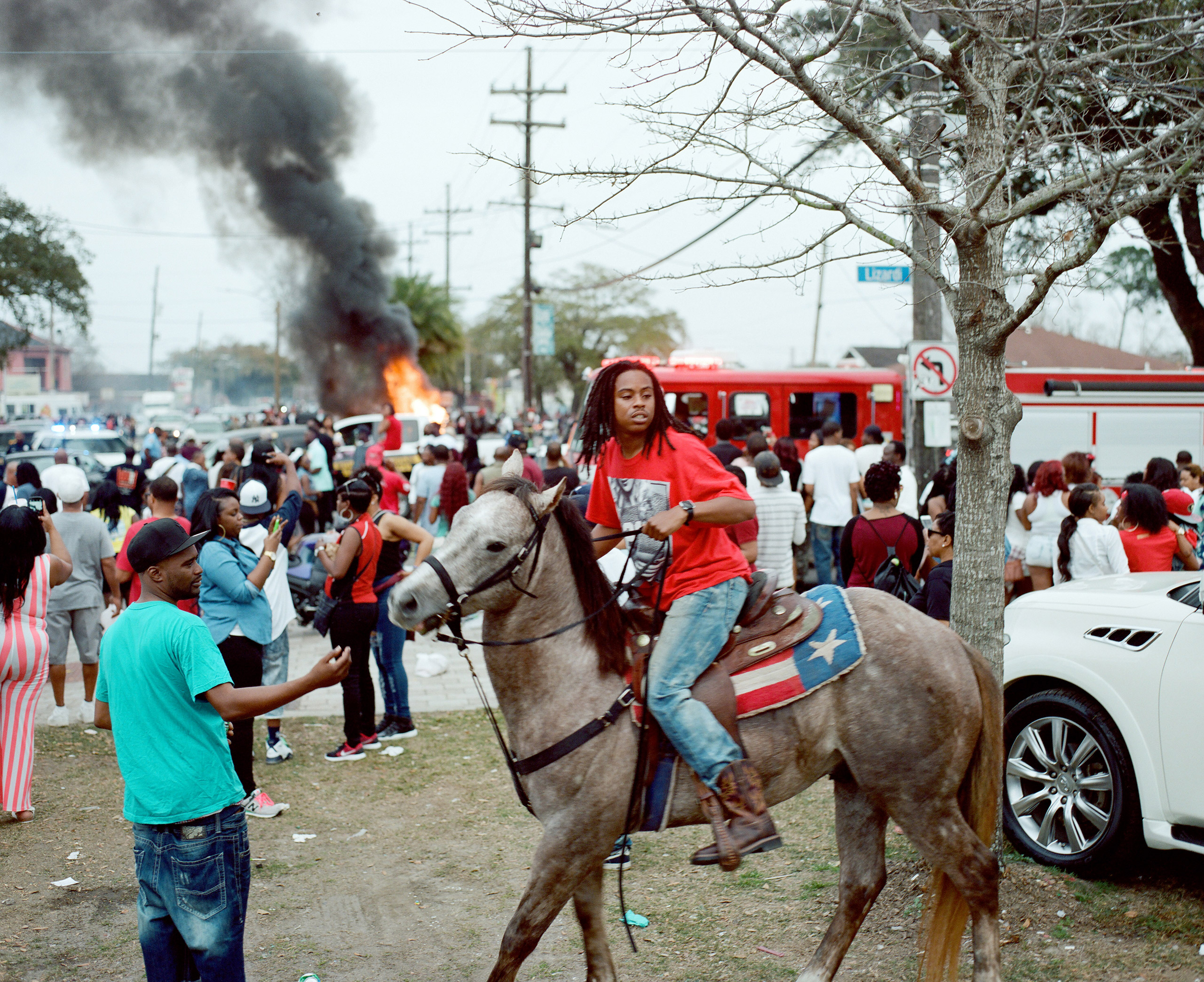 A young man on horseback at a Second Line moves away from a burning car in New Orleans, La. 2016