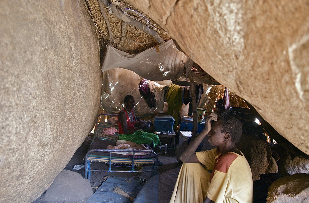 People from the Nuba Mountains in Sudan hide under boulders to escape from government bombing in April 2012.