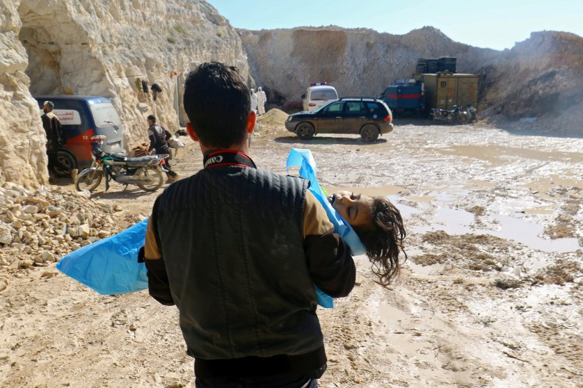 A man carries the body of a dead child, after what rescue workers described as a suspected gas attack in the town of Khan Sheikhoun, Syria, on April 4, 2017.