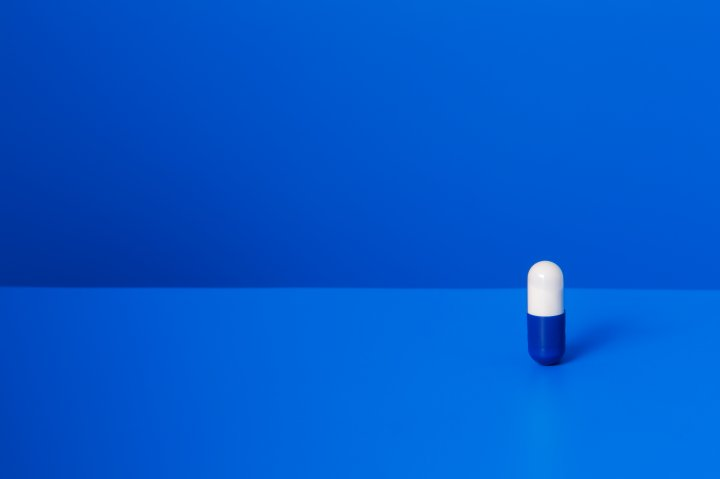 Prescription pill standing upright on blue counter TIME health