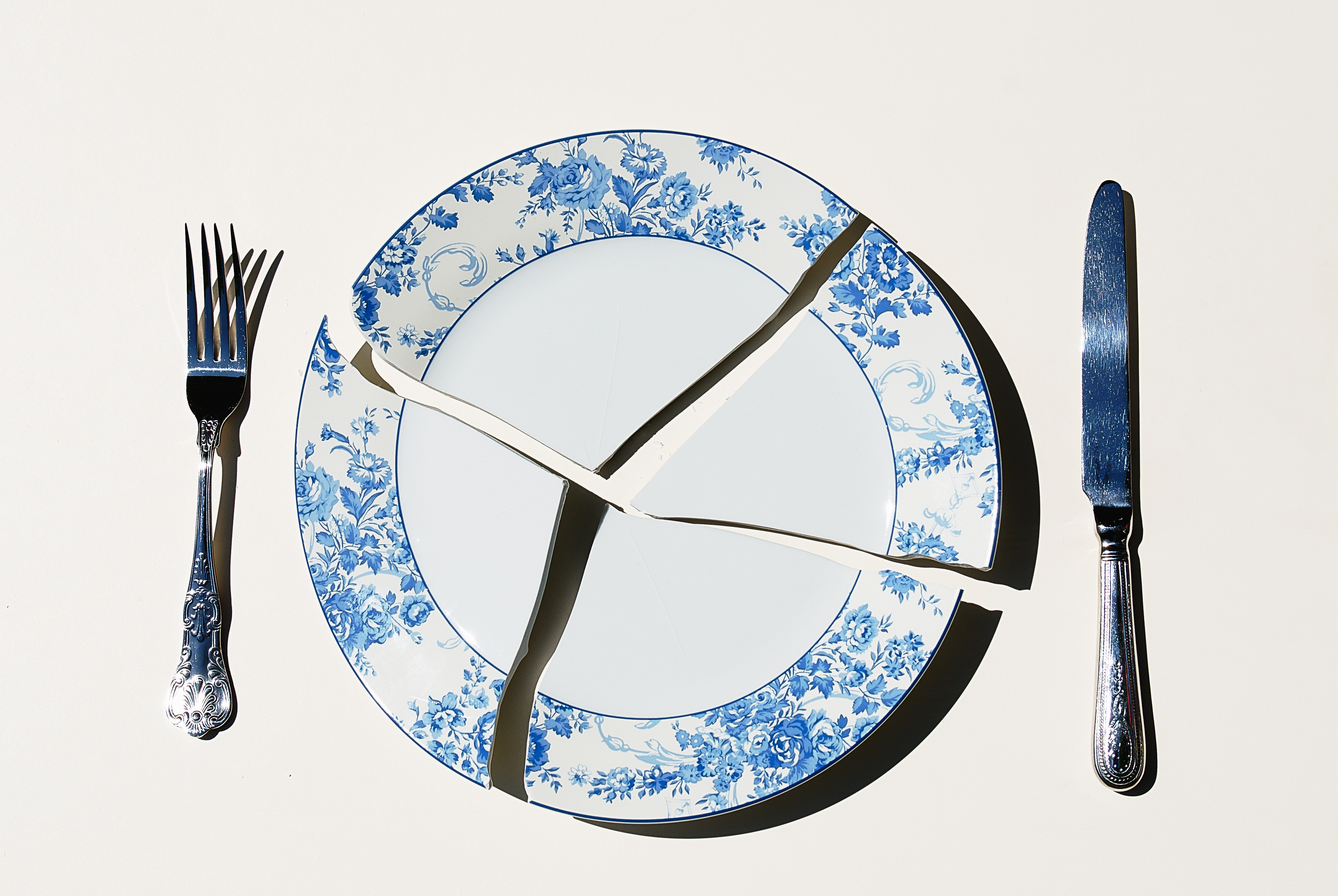 Broken plate with knife and fork on white background