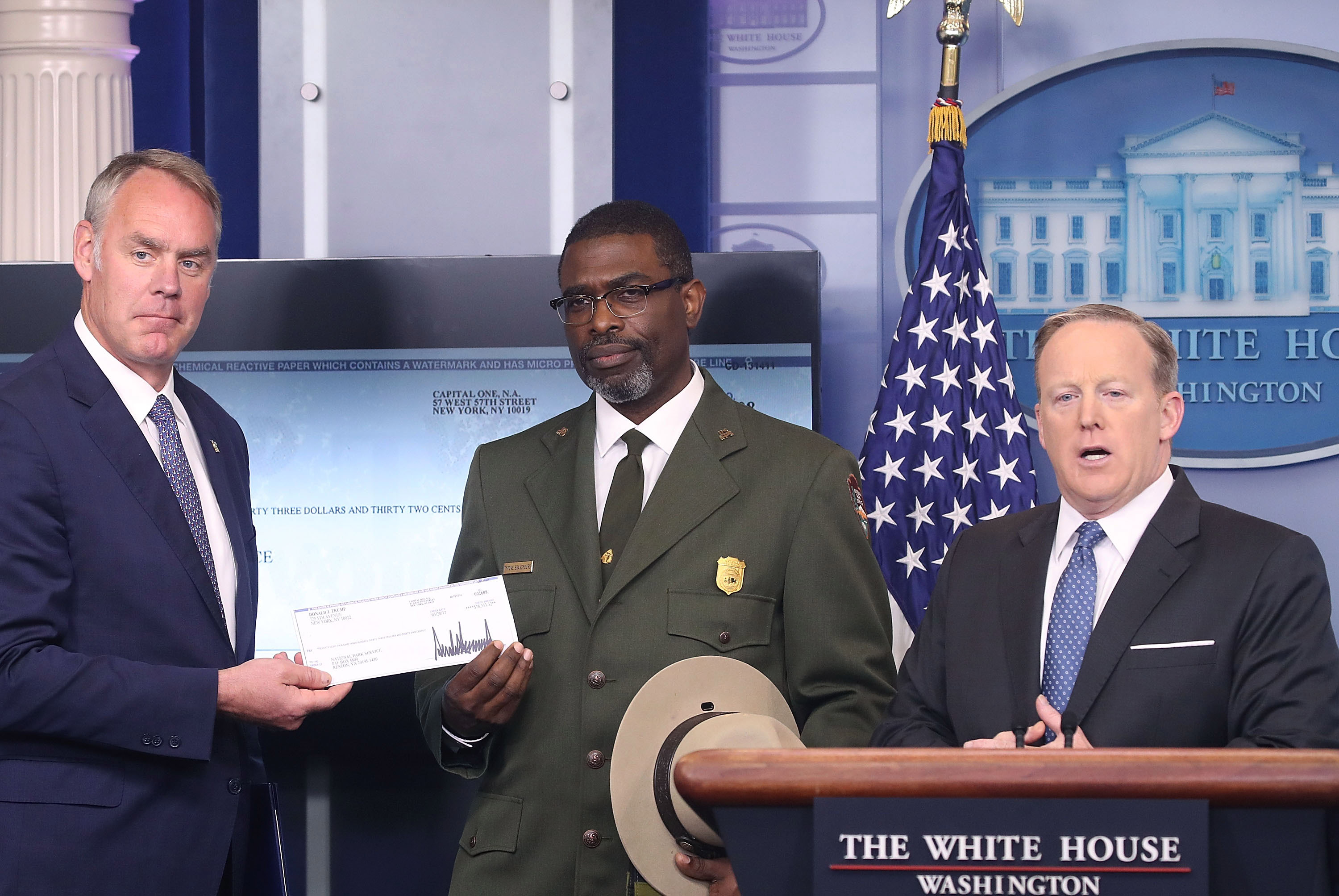White House Press Secretary Sean Spicer gave Interior Secretary Ryan Zinke (L) the first-quarter check of President Donald Trump's salary, which he donated to the National Park Service as Tyrone Brandyburg (C), Harpers Ferry National Historical Park superintendent, looks on during the daily press briefing at the White House on April 3, 2017.