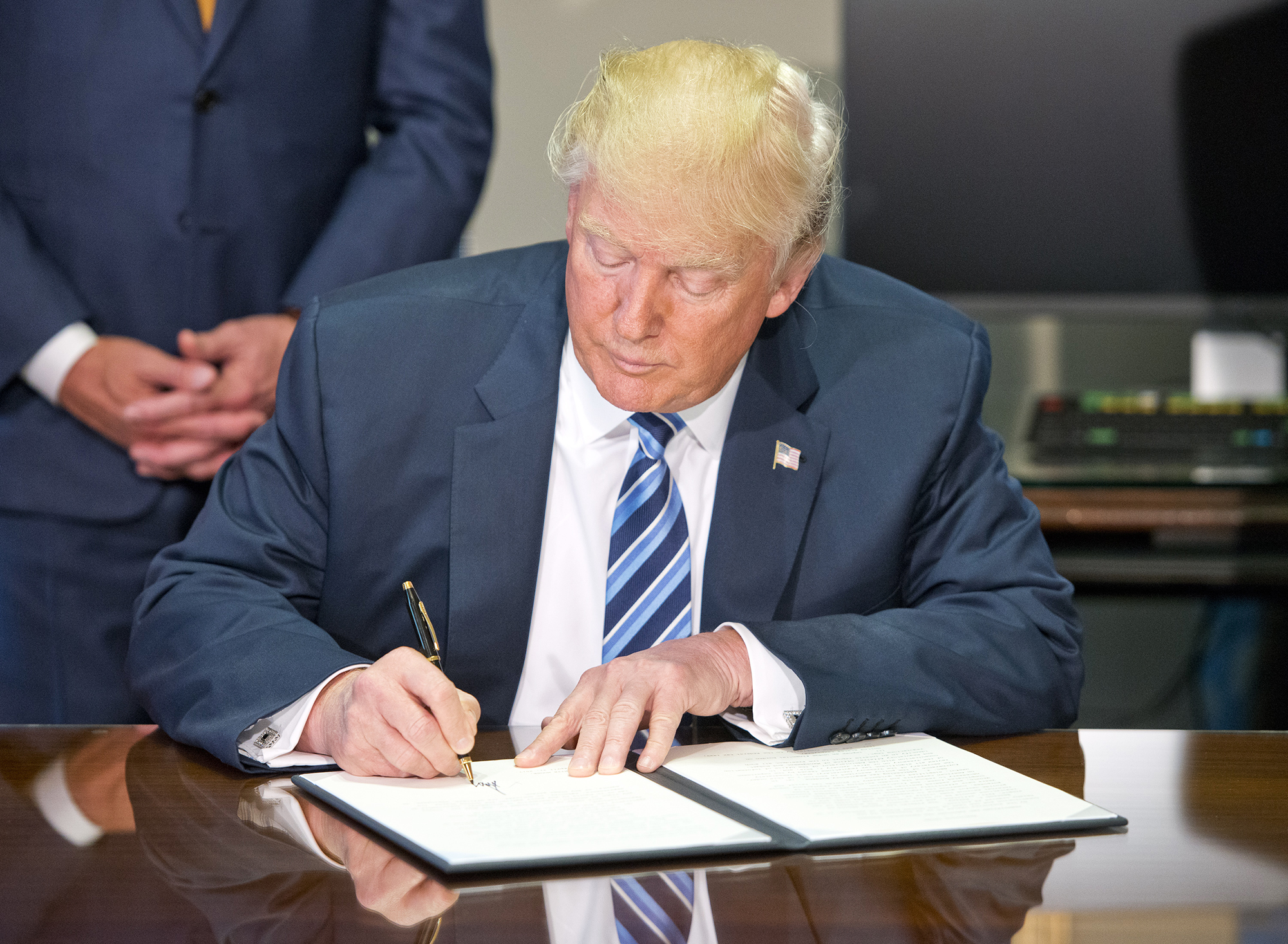 Donald Trump signs the first of three Executive Orders concerning financial services at the Department of the Treasury in Washington, D.C., on April 21, 2017.