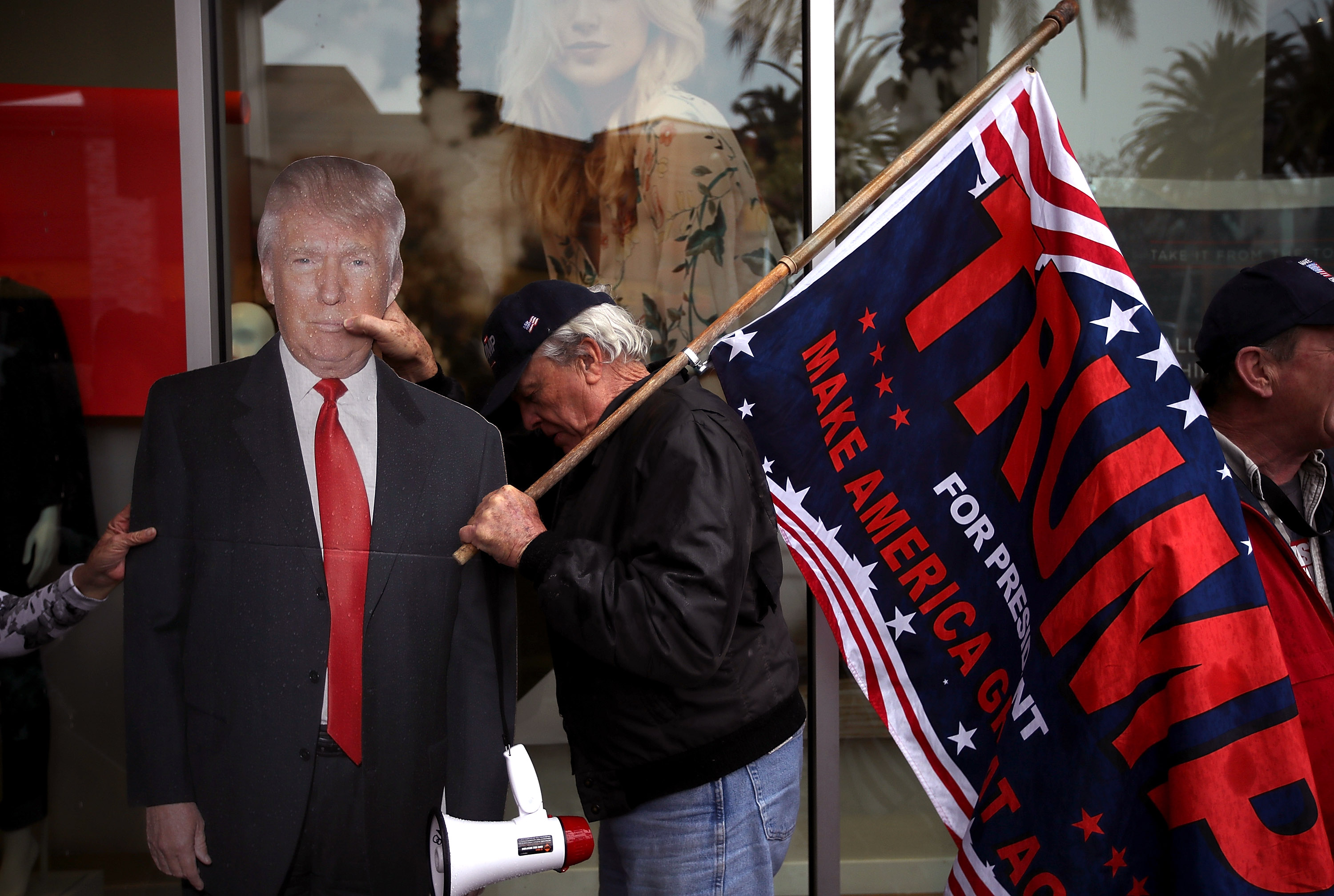A supporter of U.S. President Donald Trump move a cardboard cut out of President Trump out of the rain during a rally in favor of the  America First  agenda on February 27, 2017 in Brea, California.