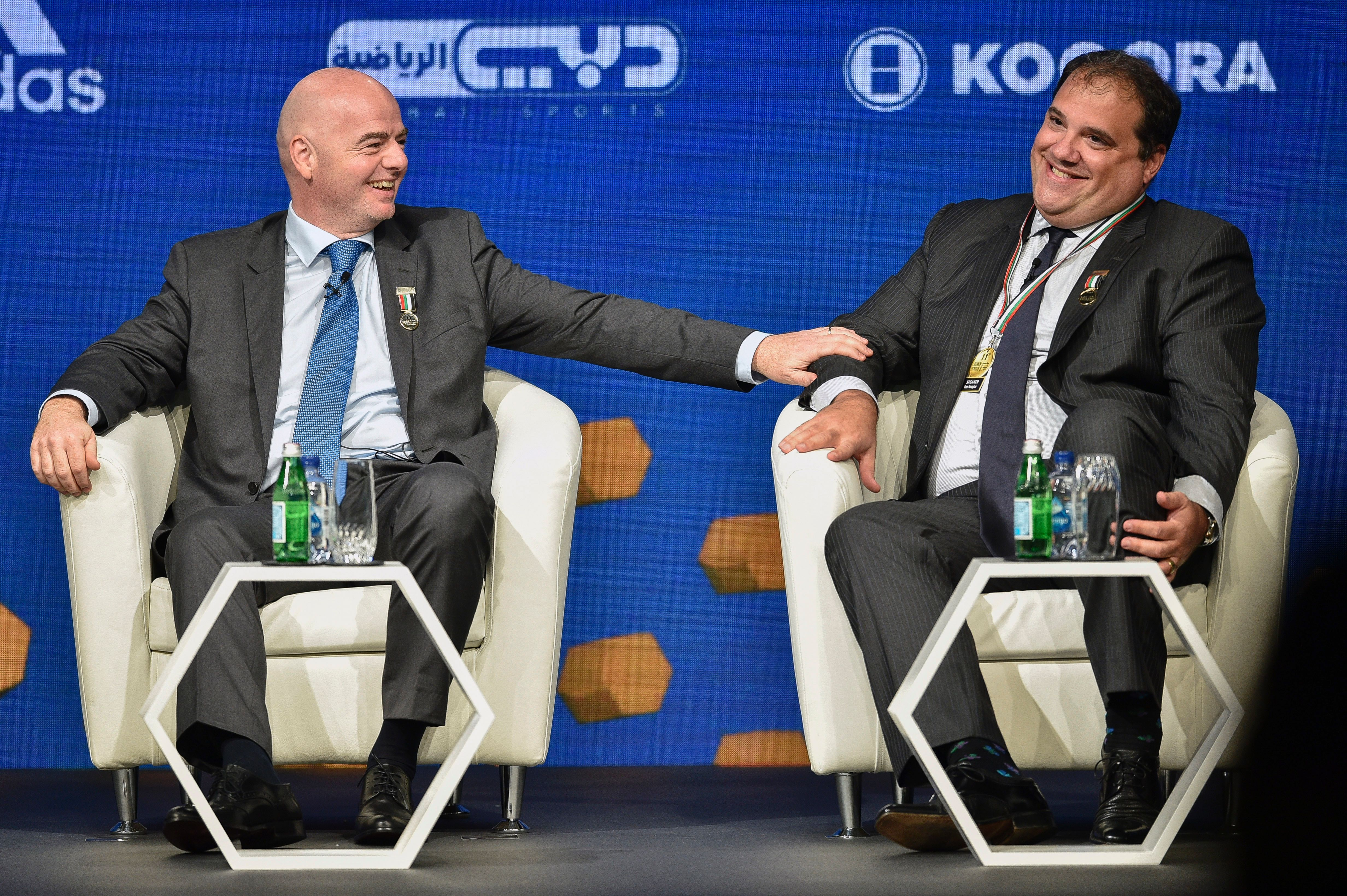 FIFA President, Gianni Infantino (L), talks with Victor Montagliani, CONCACAF President, during the Dubai international Sports conference at Madinat Jumeirah in Dubai on December 28, 2016.