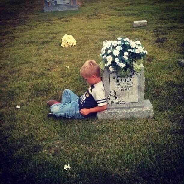 Walker Myrick leans against his late twin brother's gravestone at Center Hill Cemetery in Lexington, Ala., telling him about his first day in kindergarten.