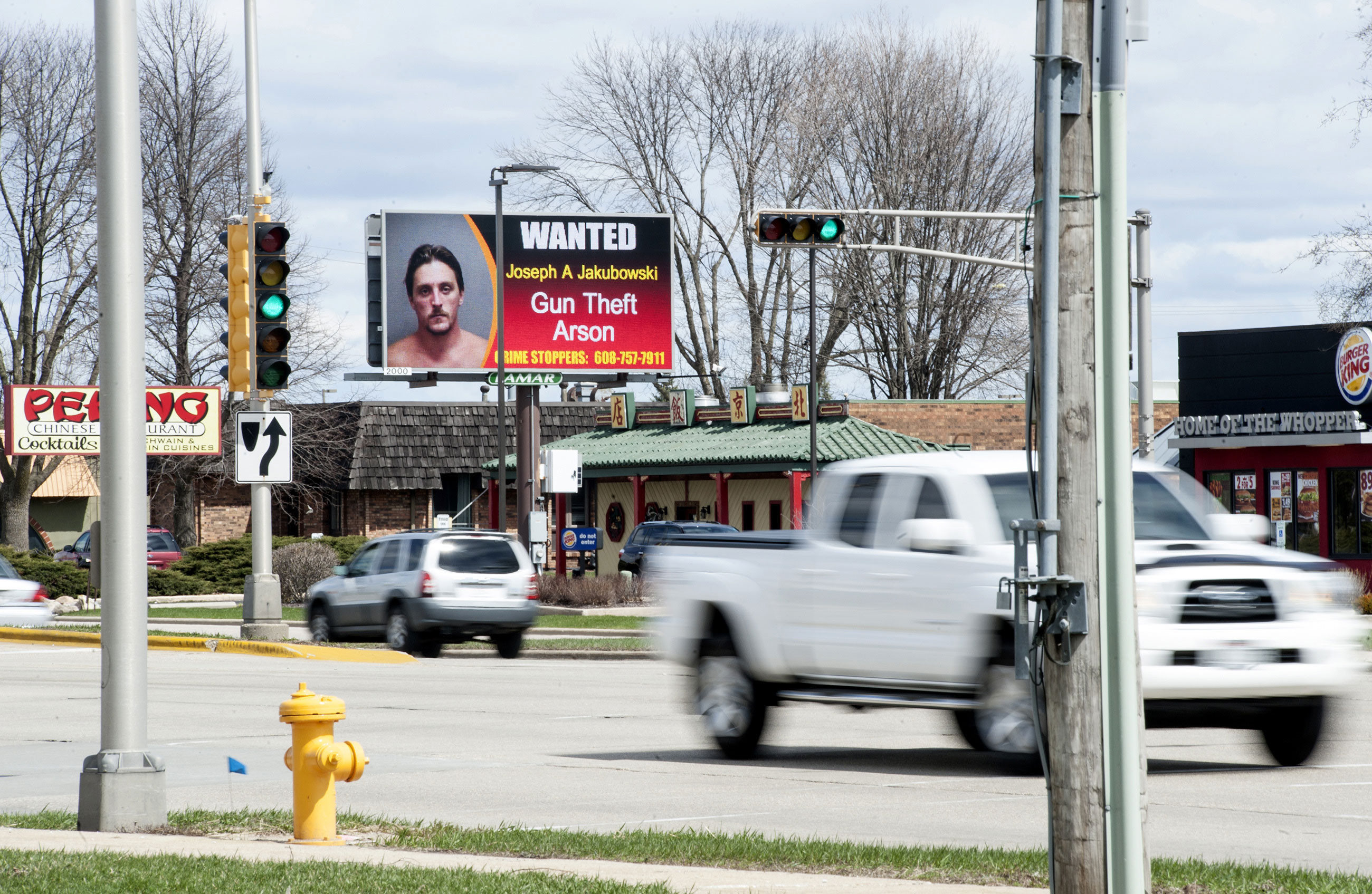 Vehicles drive by an electronic billboard in Janesville, Wis., showing a wanted sign for Joseph Jakubowski on April 6, 2017. A manhunt was underway Friday for Jakubowski suspected of stealing firearms from a southern Wisconsin gun store, threatening an unspecified attack that prompted several schools to close, and sending an anti-government manifesto to President Donald Trump.