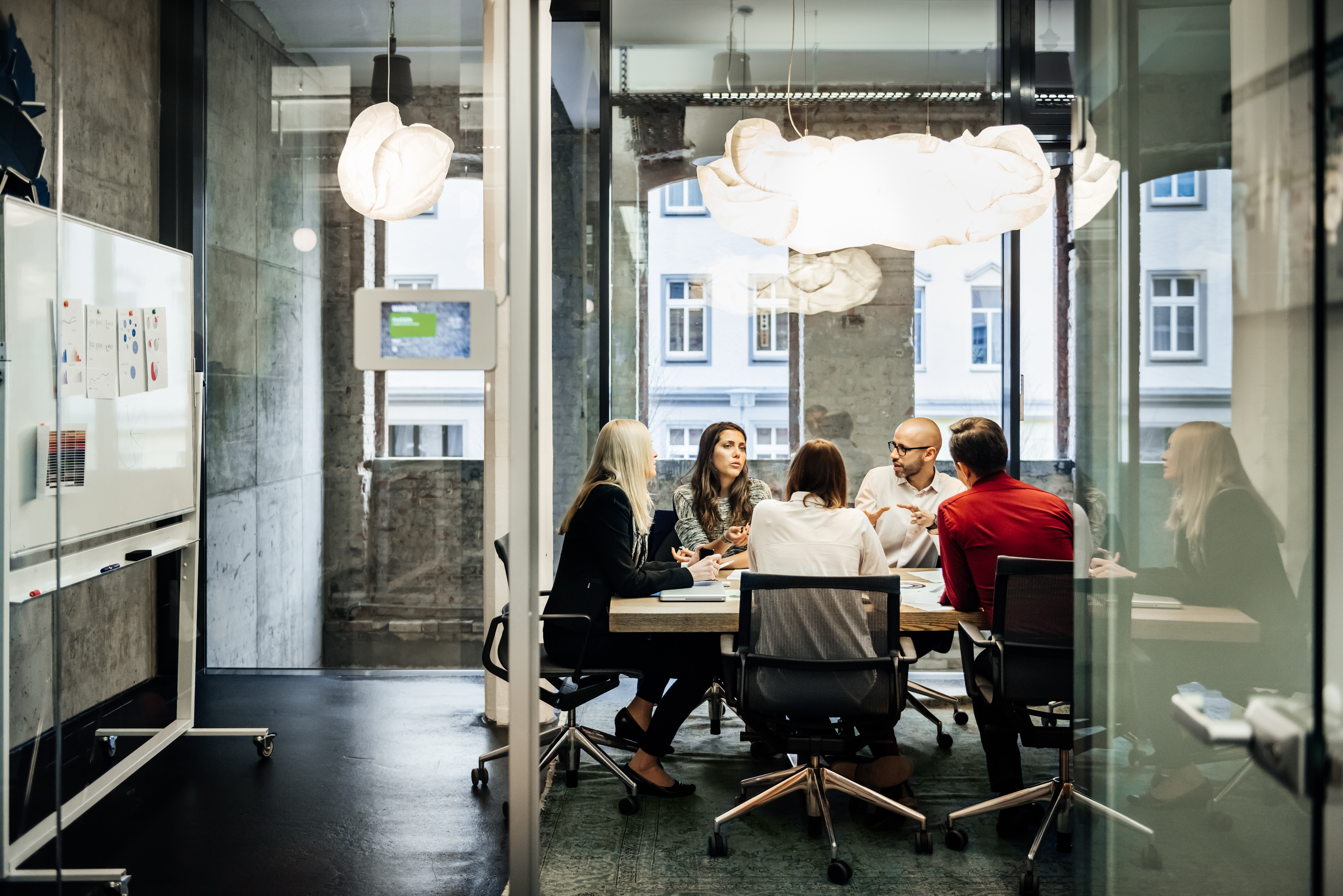 A group of people is sitting at a table during a business meeting in a bright, modern office. The team is talking business while pie charts can be seen hanging on the wall. Big bright windows are seen in the background.