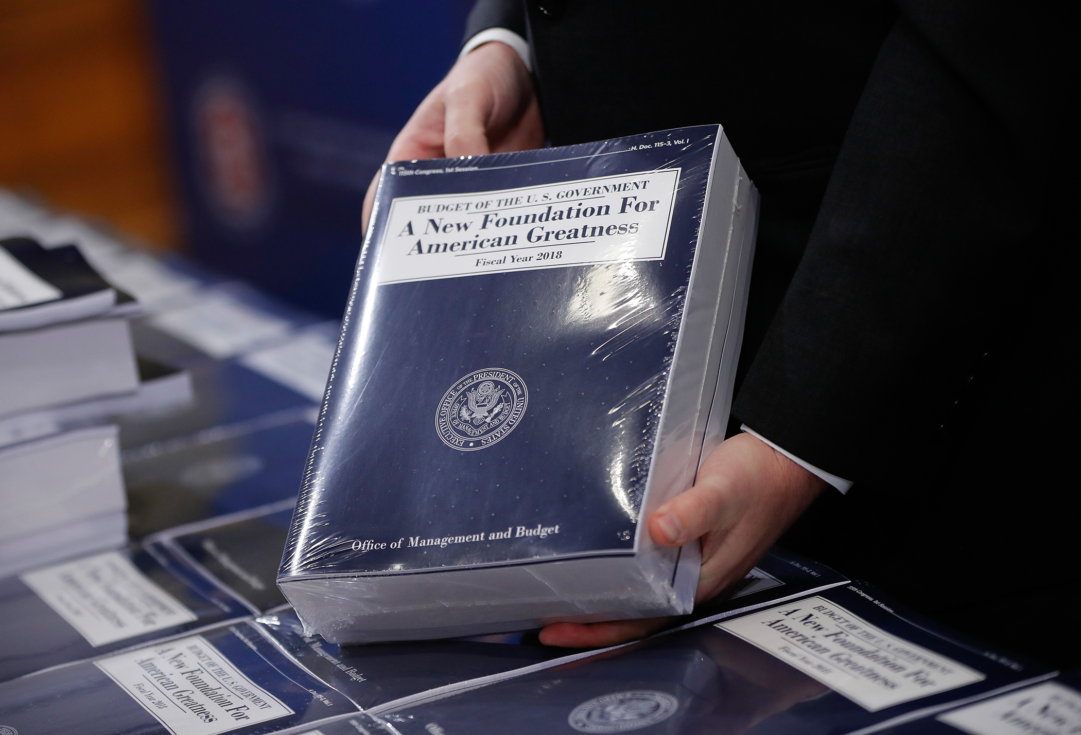 Eric Ueland, Republican staff director, Senate Budget Committee holds a copy of President Donald Trump's fiscal 2018 federal budget, before distributing them to congressional staffers on Capitol Hill in Washington, Tuesday, May 23, 2017.