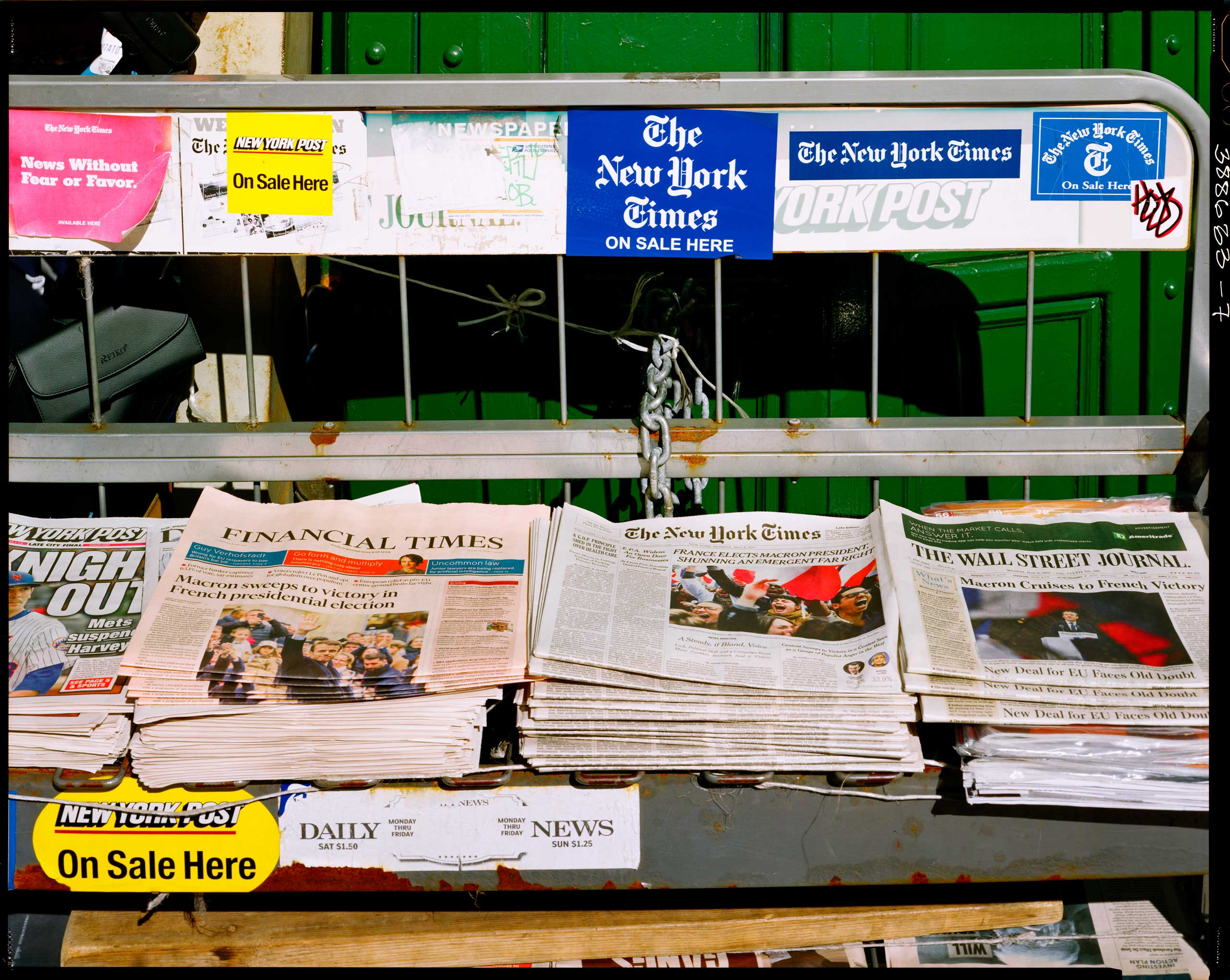 """Translation of caption from Liberation: May 8, 9 am, Union Square. It's one of the rare remaining newsstands in the city. This morning, even the New York Post's headline talks of the French election """"FRANCE'S NEW LEADER, MACRON: Oui did it!"""" For the New York Times, it's """"SHUNNING AN EMERGENT FAR RIGHT."""" France has elected Macron as its president while rejecting the emerging far right. Same story for the Wall Street Journal and the Financial Times: """"MACRON CRUISES TO FRENCH VICTORY"""" and """"MACRON SWEEPS TO VICTORY"""". Macron sails to a victory and wins the presidential election. The city is in a good mood. It's chilly out, but the sun is shining."""