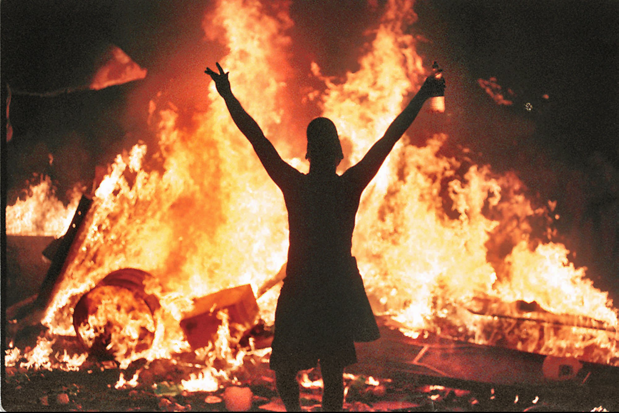 A man stands in front of a bonfire at the 1999 Woodstock Festival, Sunday, July 25, 1999, in Rome, N.Y. After almost 72 hours of peace and love, Woodstock '99 ended in blazing chaos Sunday night as hundreds of concertgoers turned into vandals, starting fires and looting.