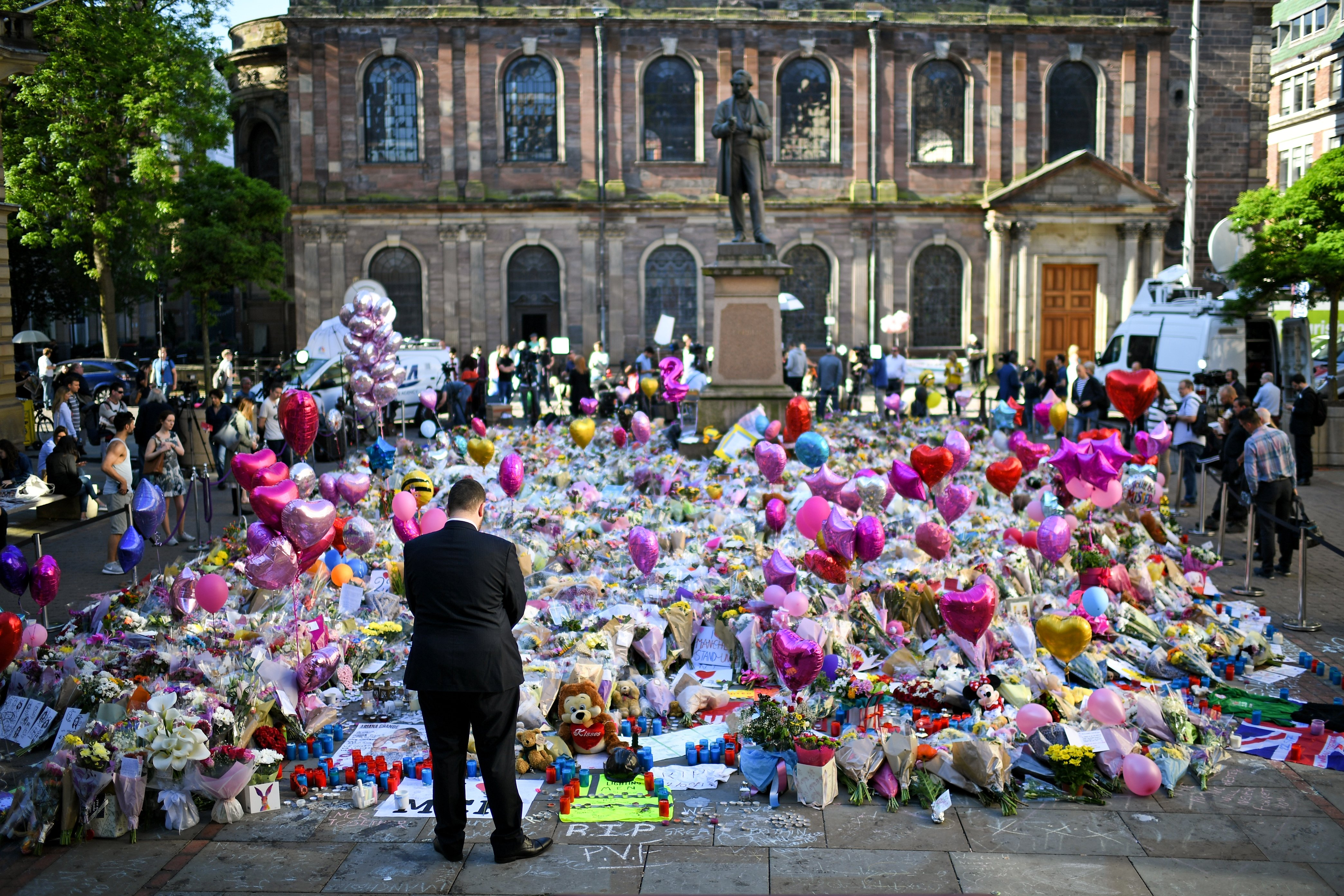 Members of the public look at tributes left in St Ann's Square for the people who died in Monday's terror attack at the Manchester Arena on May 26, 2017 in Manchester, England.