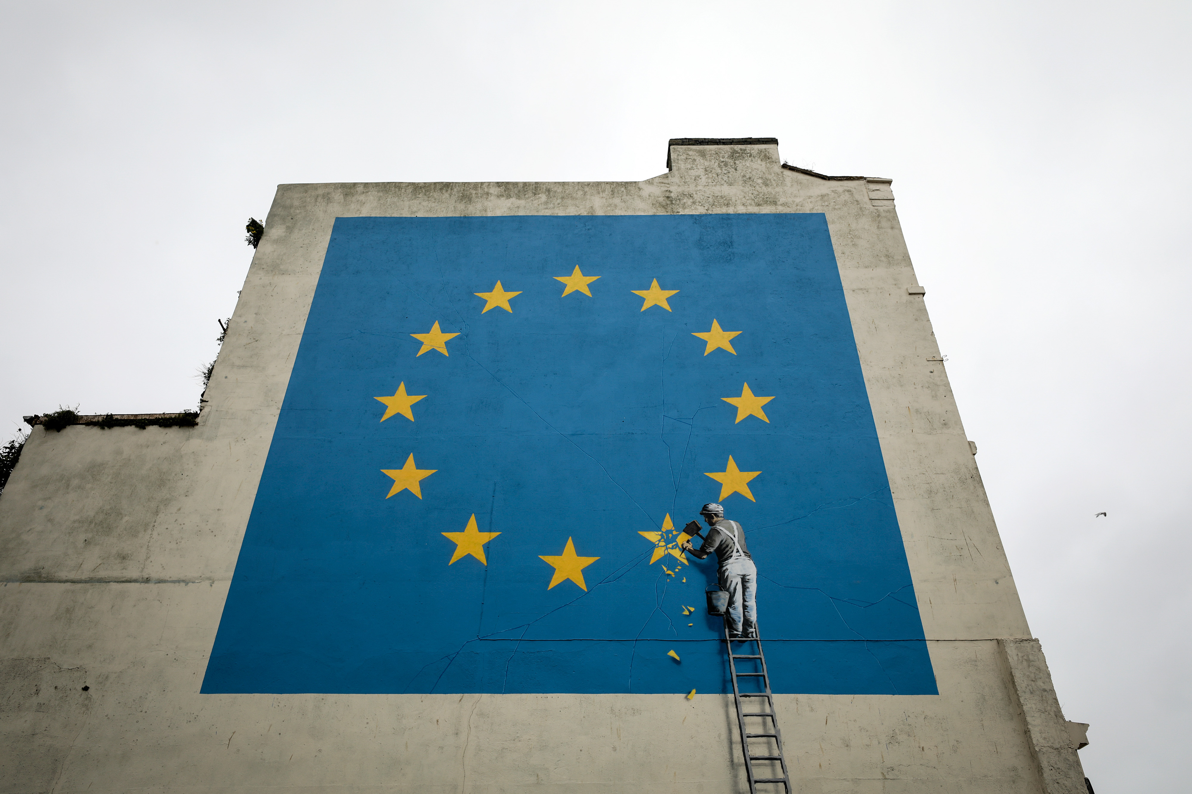A mural depicting a European Union (EU) flag being chiseled by a workman sits on the side of a disused building near the ferry terminal in Dover, U.K., on Monday, May 8, 2017.
