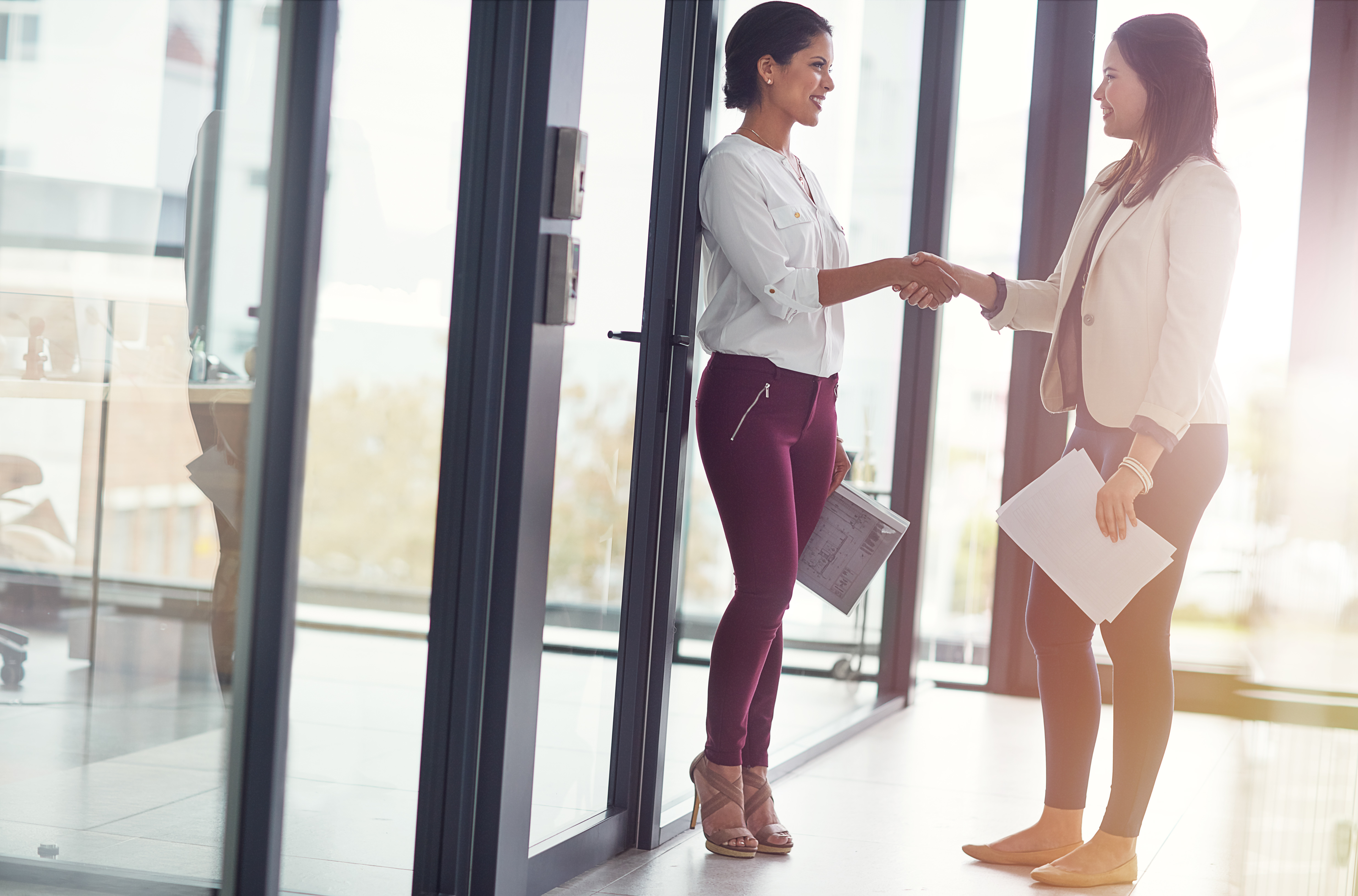 Shot of two businesswomen shaking hands in an office