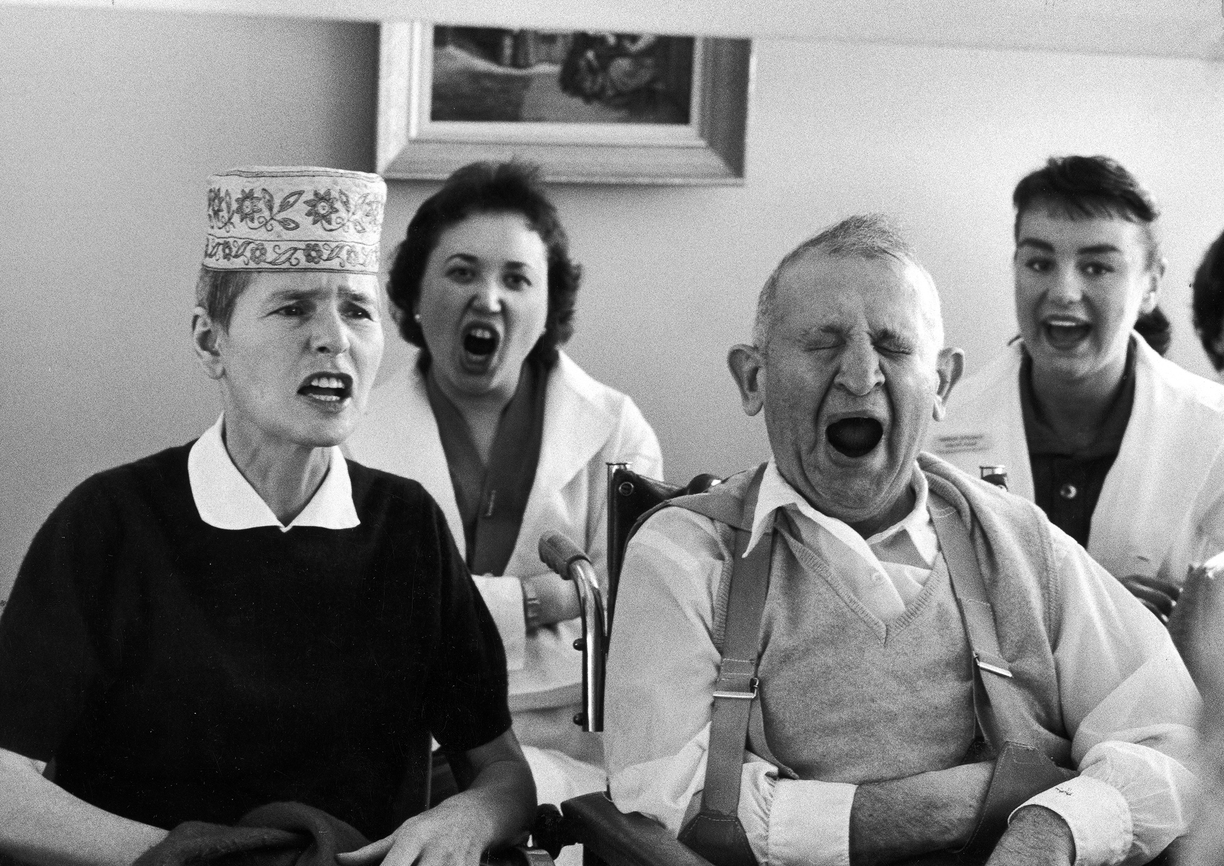 Caption from LIFE. Straining to relearn how to speak distinctly after disease had blurred and weakened her voice, the author, with another patient, is taught by therapists (rear) to exaggerate lip movements.