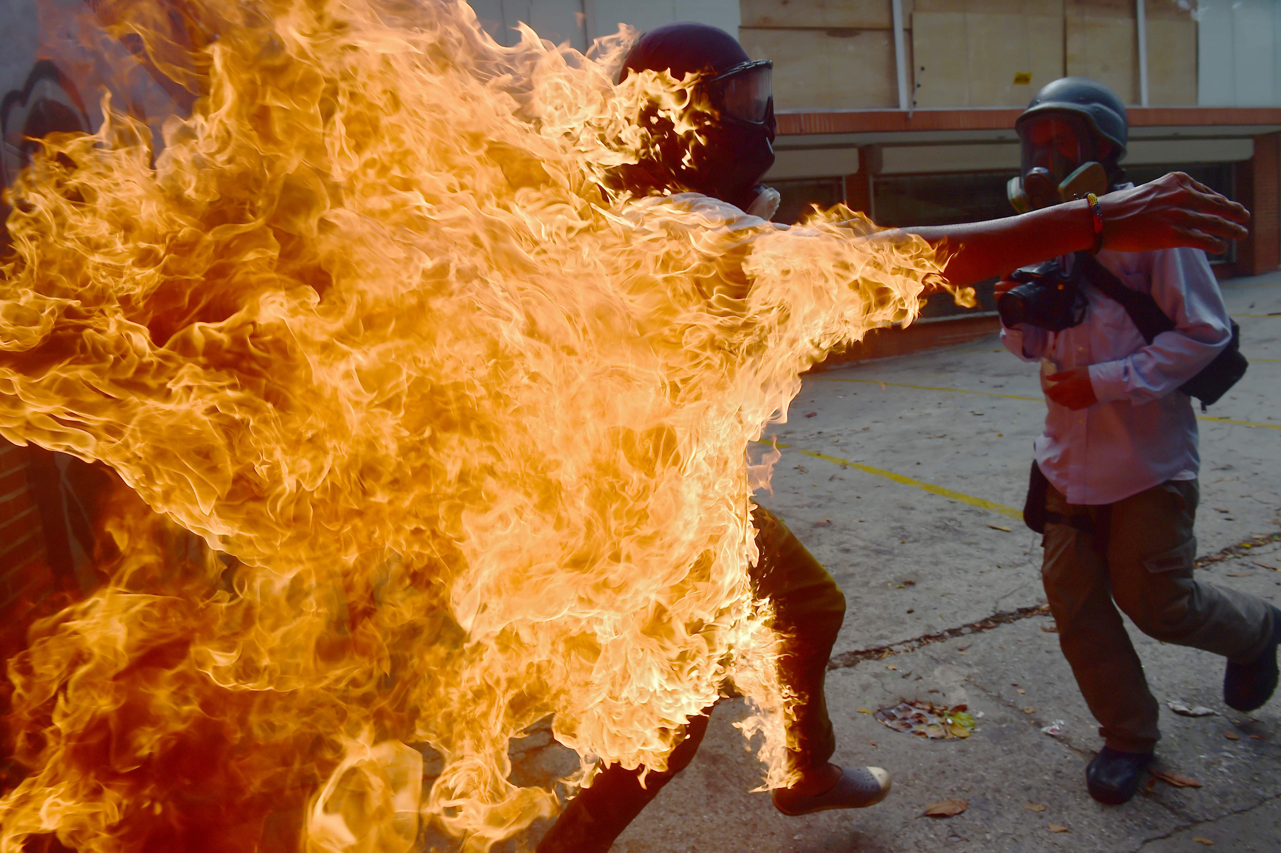 A man set ablaze during an anti-Maduro protest runs to put out the flames in Caracas on May 3, 2017.