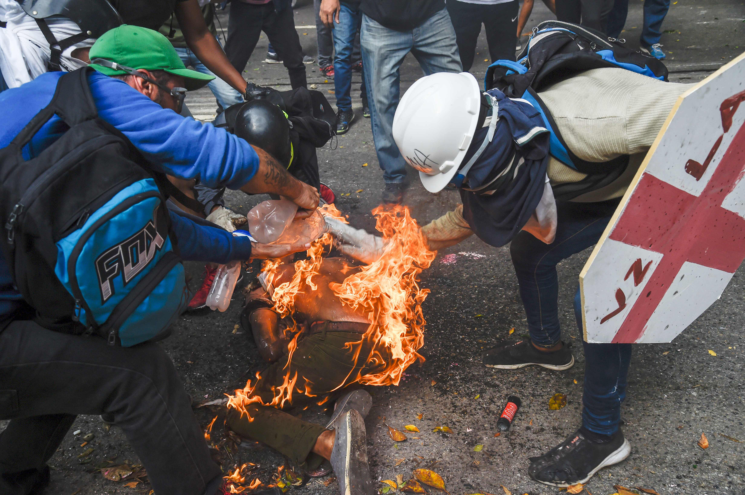 Men aid a demonstrator who caught fire during clashes in Caracas on May 3, 2017.