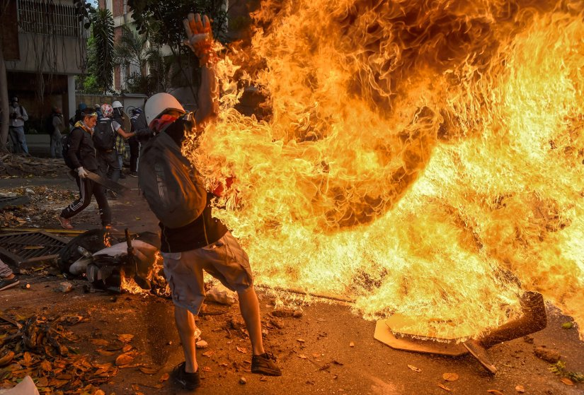 A man is engulfed in flames after the gas tank of a motorbike explodes in Caracas on May 3, 2017.