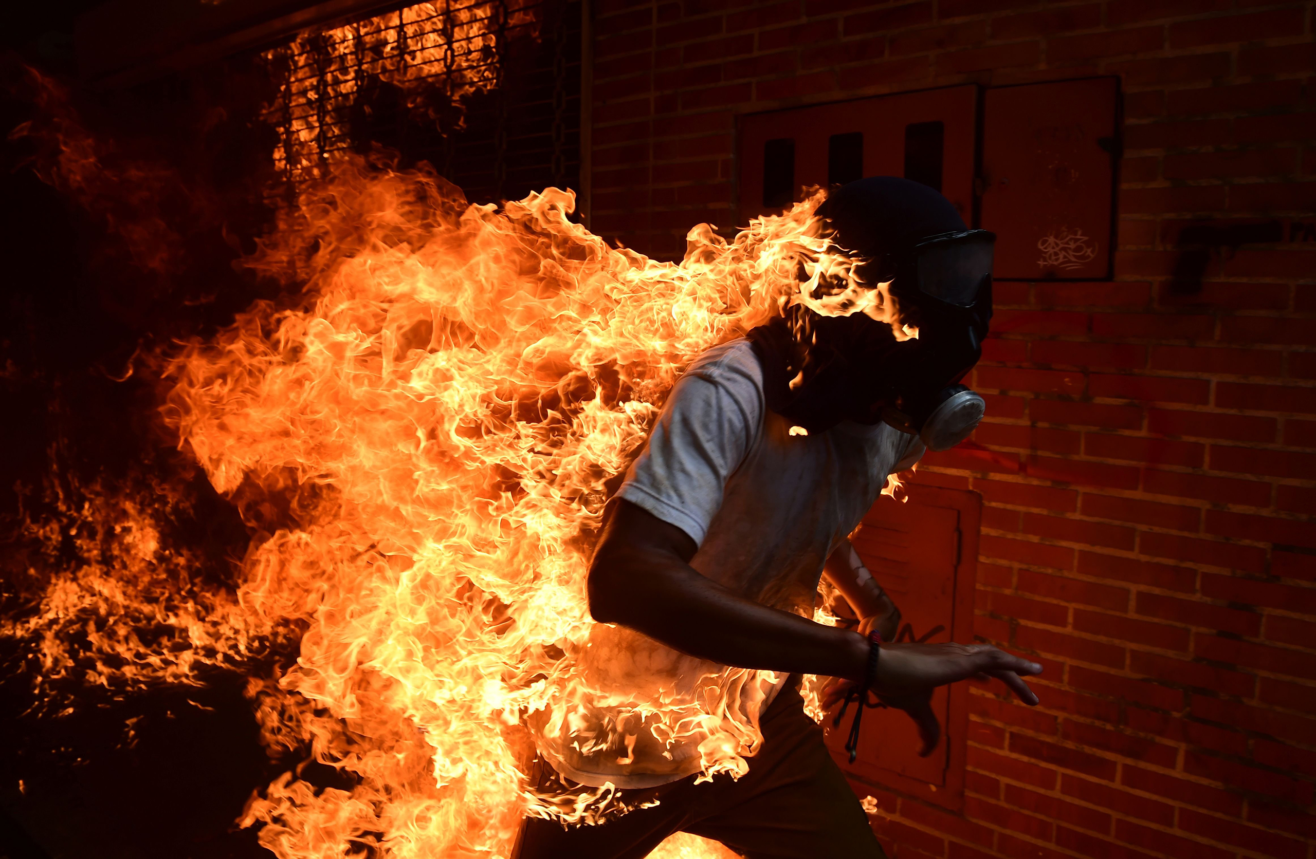 A man set ablaze runs during an anti-Maduro protest in Caracas on May 3, 2017.