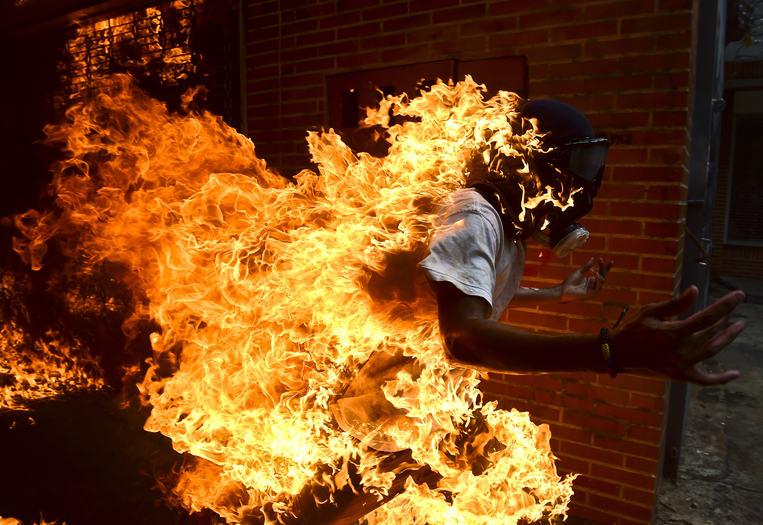 A demonstrator set ablaze runs during an anti-Maduro protest in Caracas on May 3, 2017.