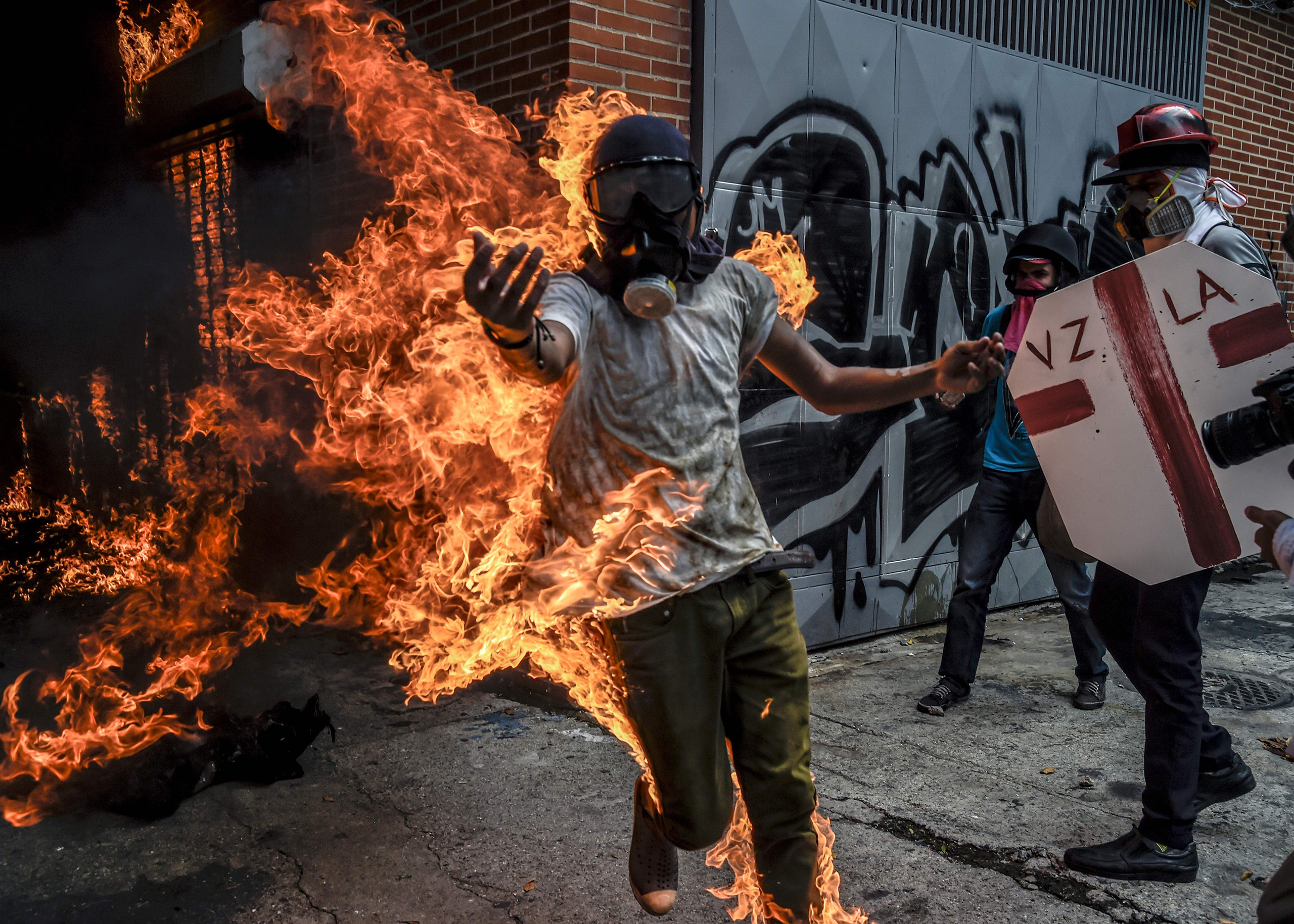 A demonstrator set ablaze during an anti-Maduro protest reaches out in Caracas on May 3, 2017.