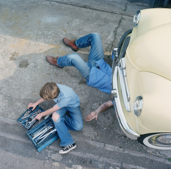 Man under car holding hand out to boy with toolbox, elevated view