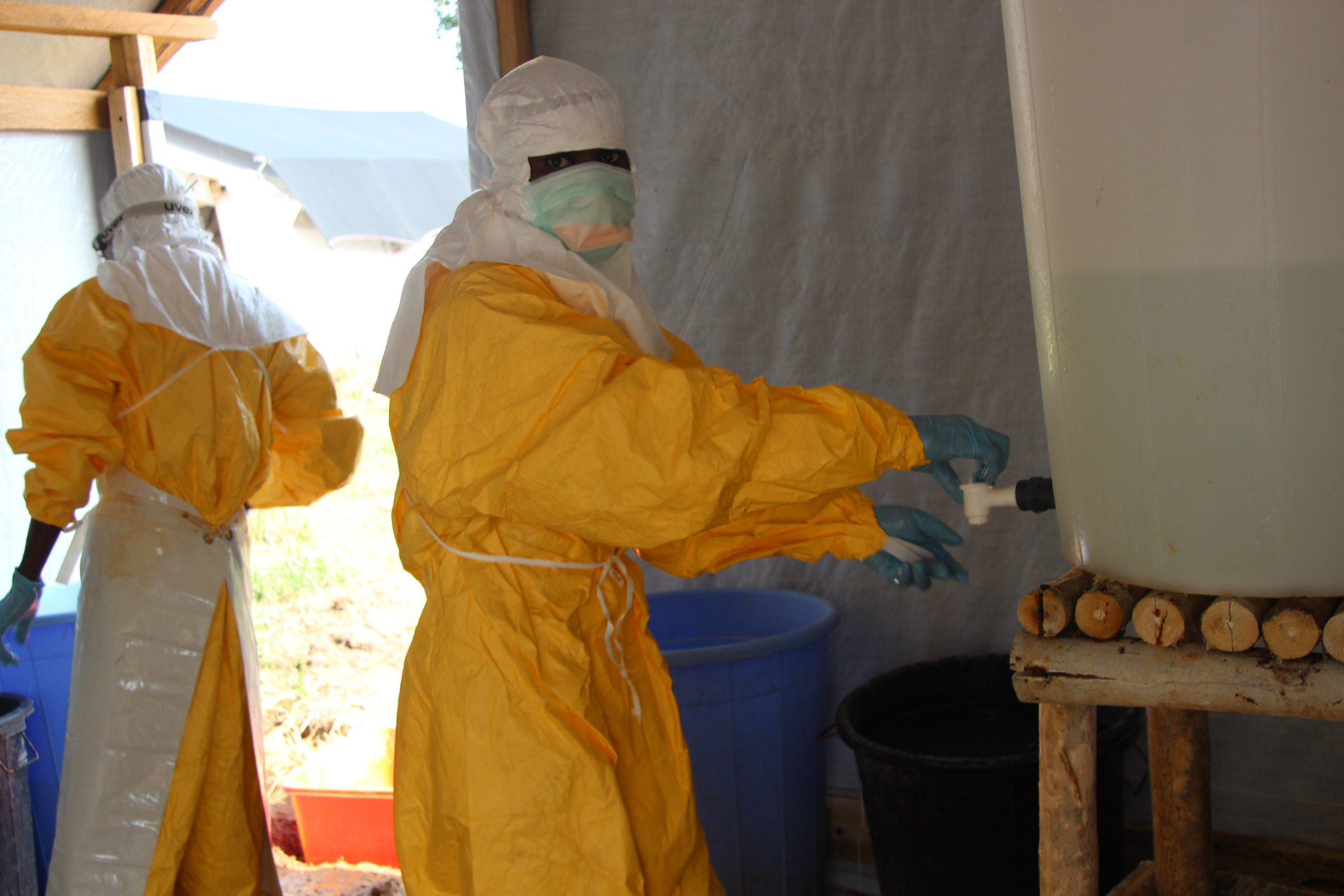 Hygienists wearing protective suits disinfect the toilets of the Ebola treatment centre in Lokolia, on October 5, 2014.