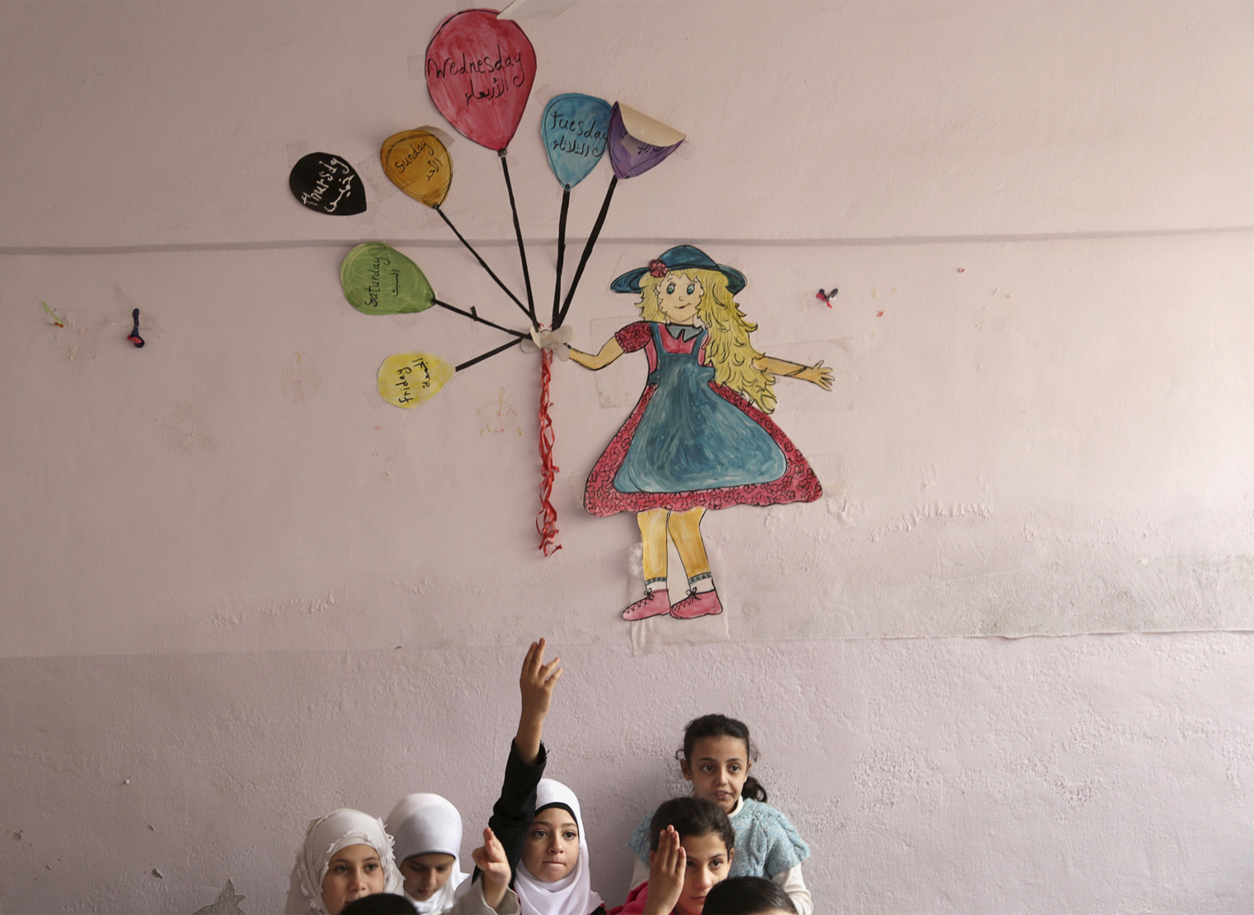 Students attend a class inside Hosam Kamel school in the rebel-controlled area of Maaret al-Numan town in Idlib province, Syria on October 28, 2015. The school, which was bombed and partially destroyed, started the new school year after restoration work was completed, activists said.