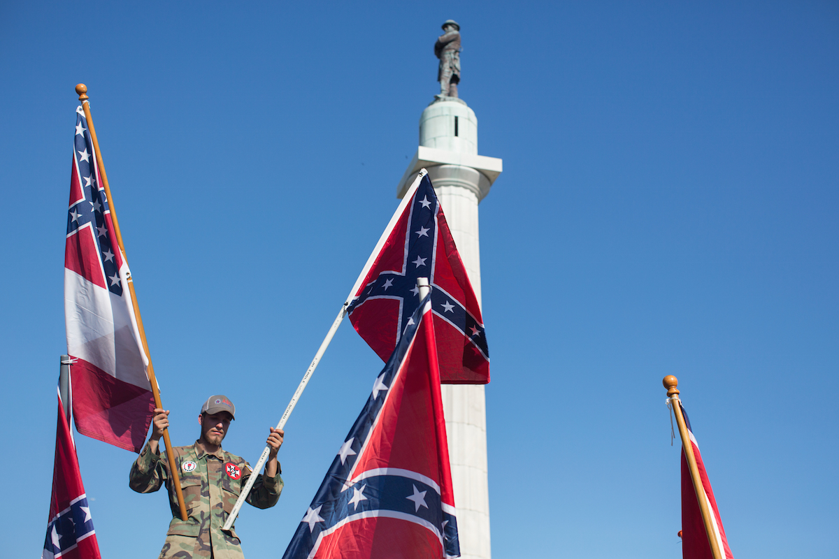 A person in opposition to the removal of monuments to the Confederacy holds confederate flags against the Robert E. Lee statue in New Orleans on May 7, 2017.