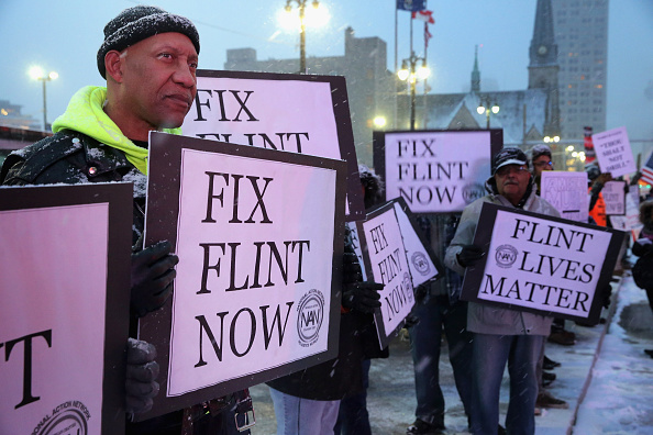 Demonstrators demand action from the Republican presidential candidates about the water crisis in Flint outside the historic Fox Theater before the GOP presidential debate March 3, 2016 in Detroit, Michigan.