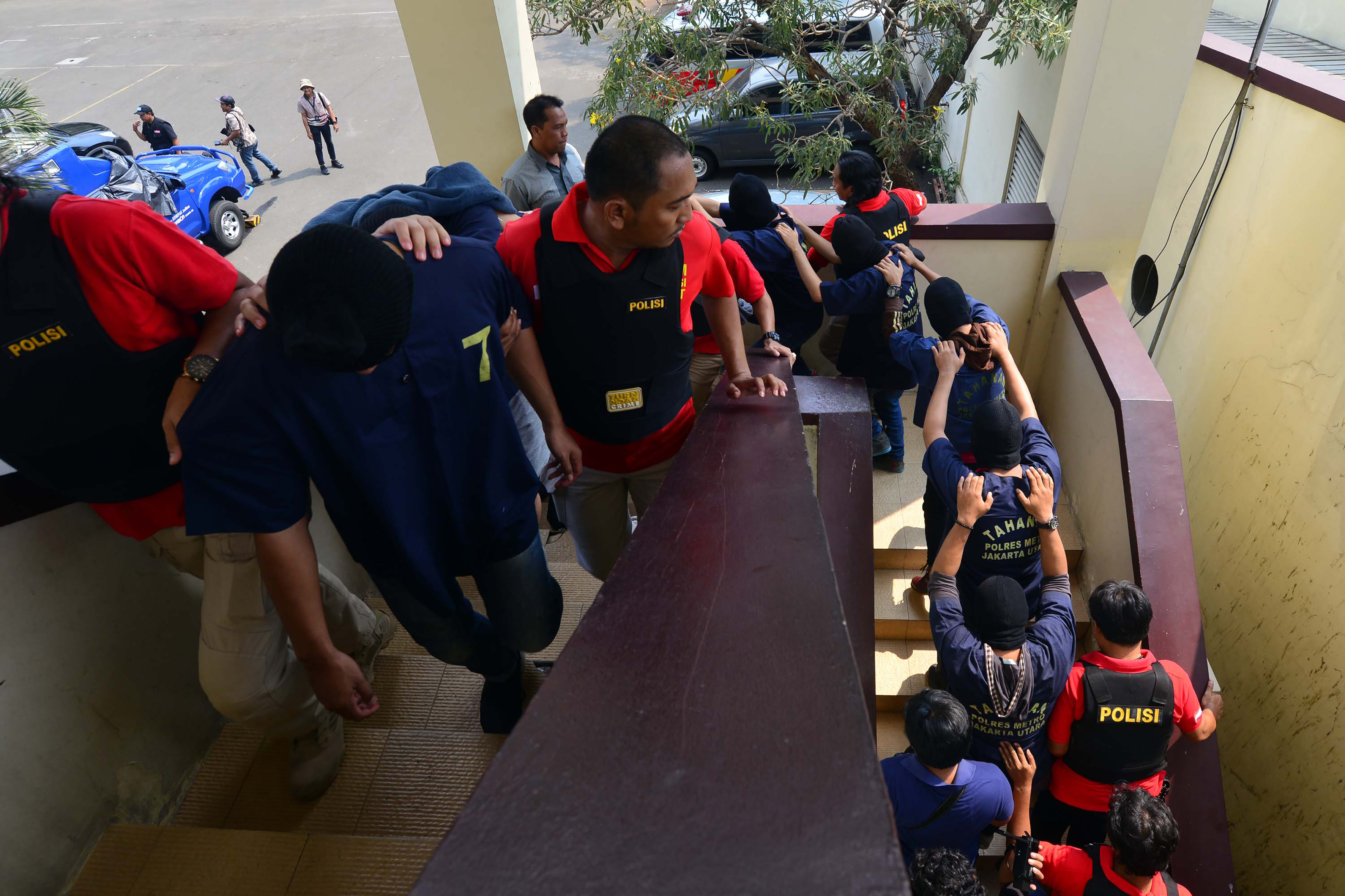 Indonesian police guard men arrested in a recent raid during a press conference at a police station in Jakarta on May 22, 2017.