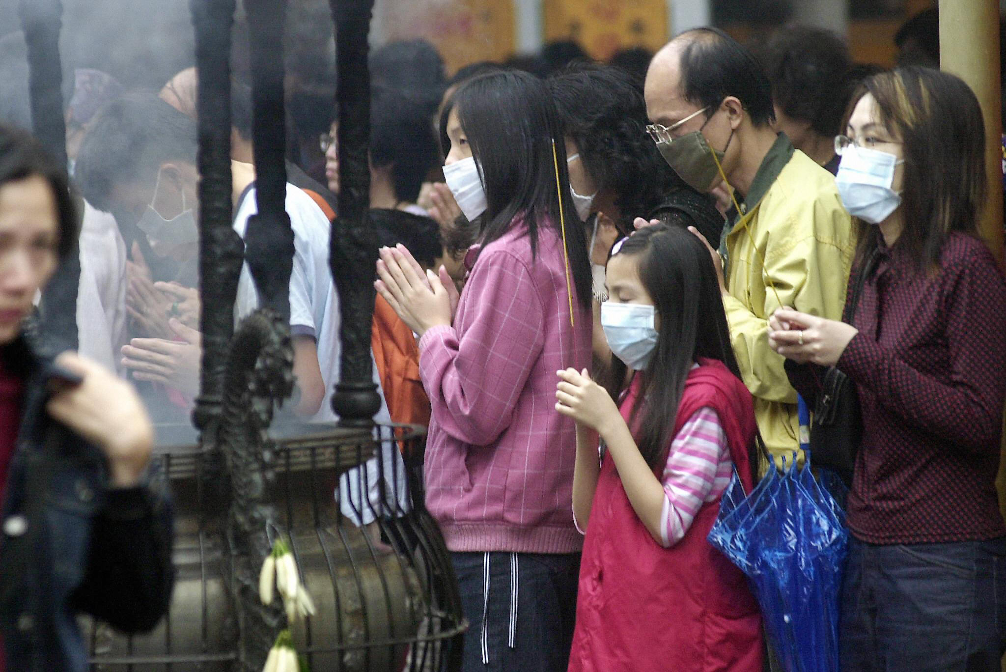 A group of Taiwanese wear face masks to protect themselves against infection from Severe Acute Respiratory Syndrome (SARS) while praying at Hsing Tien Kung Taoist temple in Taipei, in this file photo from May 18 2003.