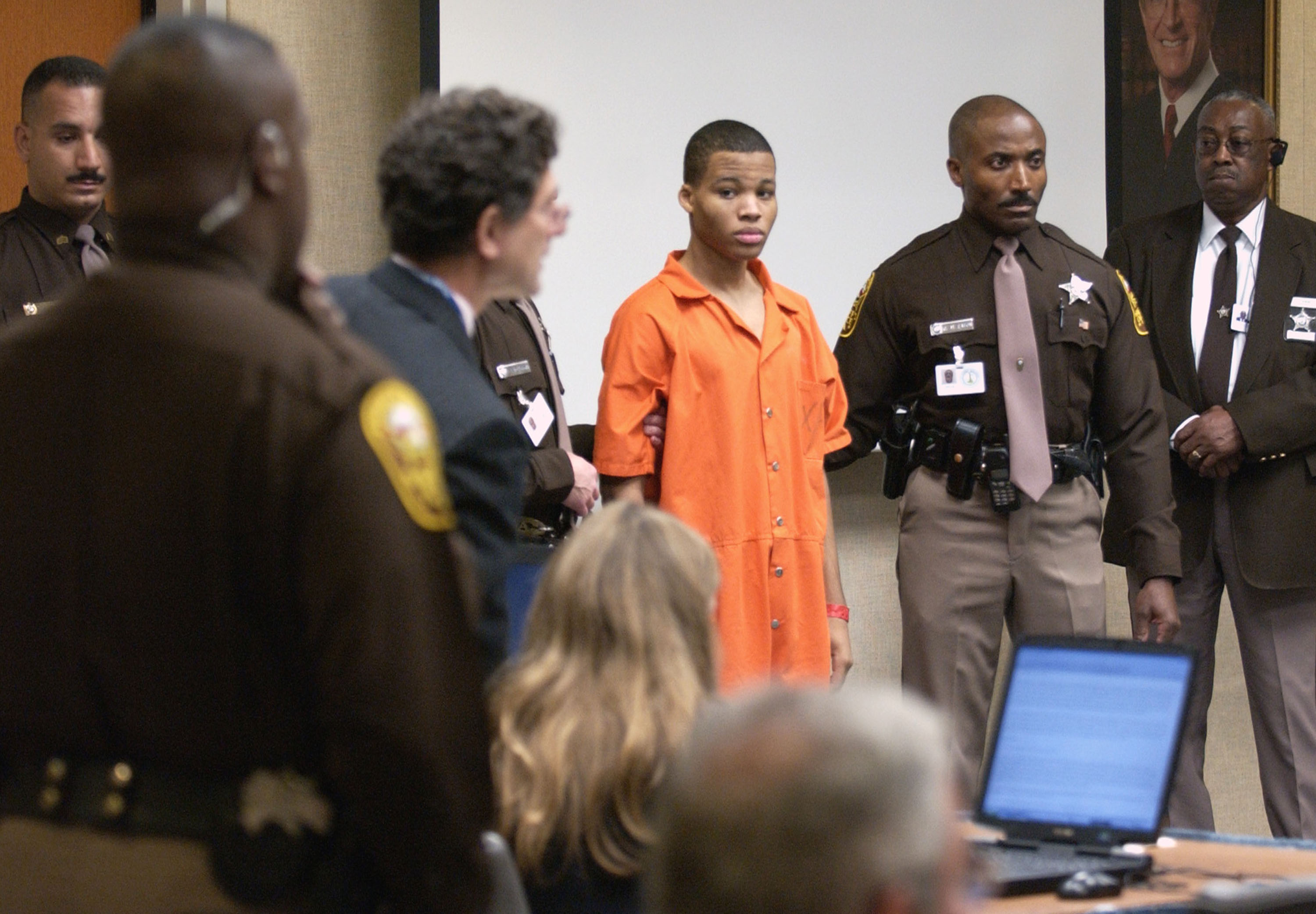 Sniper suspect Lee Boyd Malvo (C) is escorted by deputies as he is brought into court to be identified by a witness during the murder trial in courtroom 10 at the Virginia Beach Circuit Court October 22, 2003 in Virginia Beach, Virginia. Muhammad has decided not to represent himself in court and to turn his defense back to his attorneys.