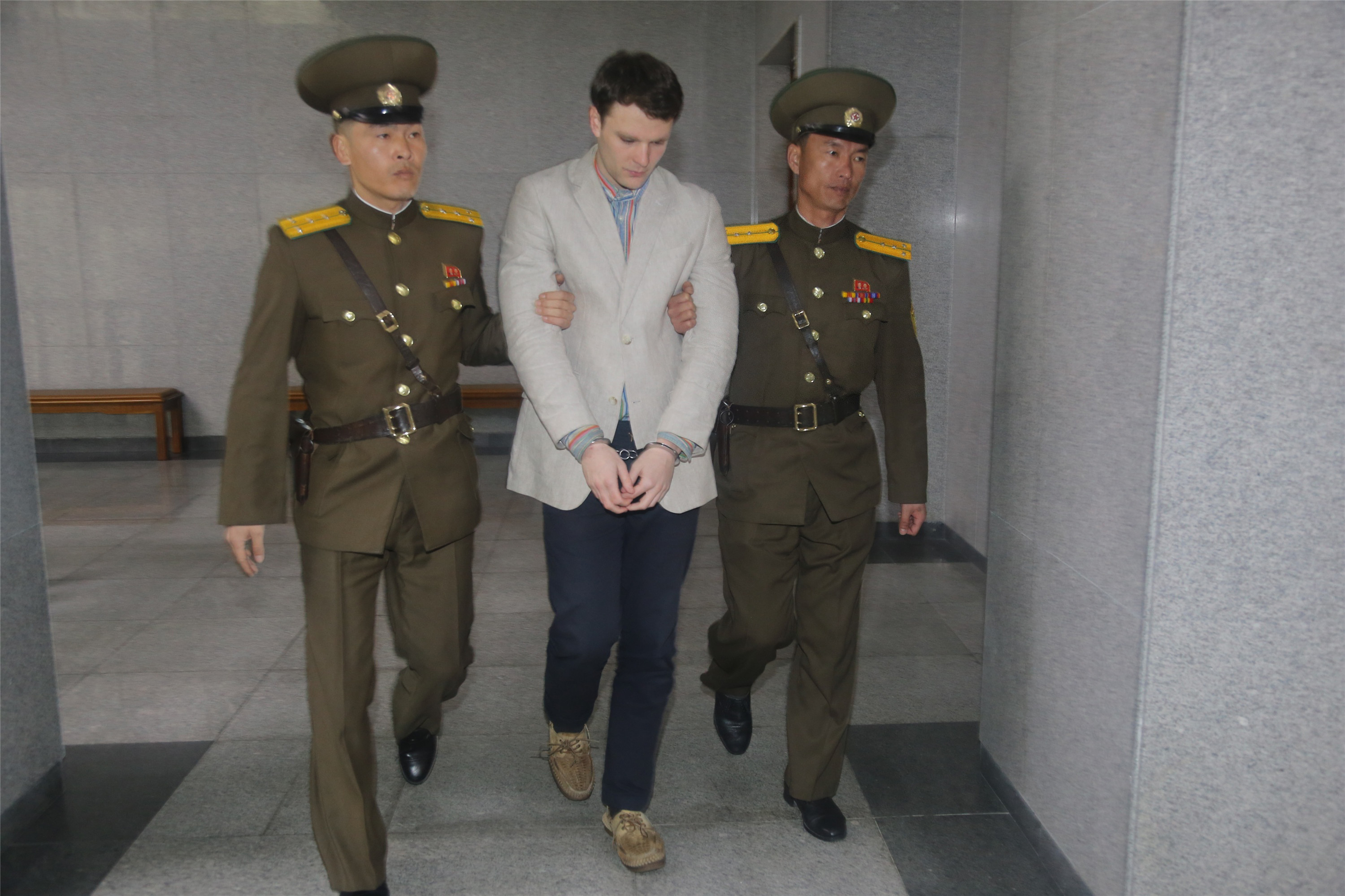 American student Otto Frederick Warmbier, center, arrives at a court for his trial in Pyongyang on March 16, 2016.