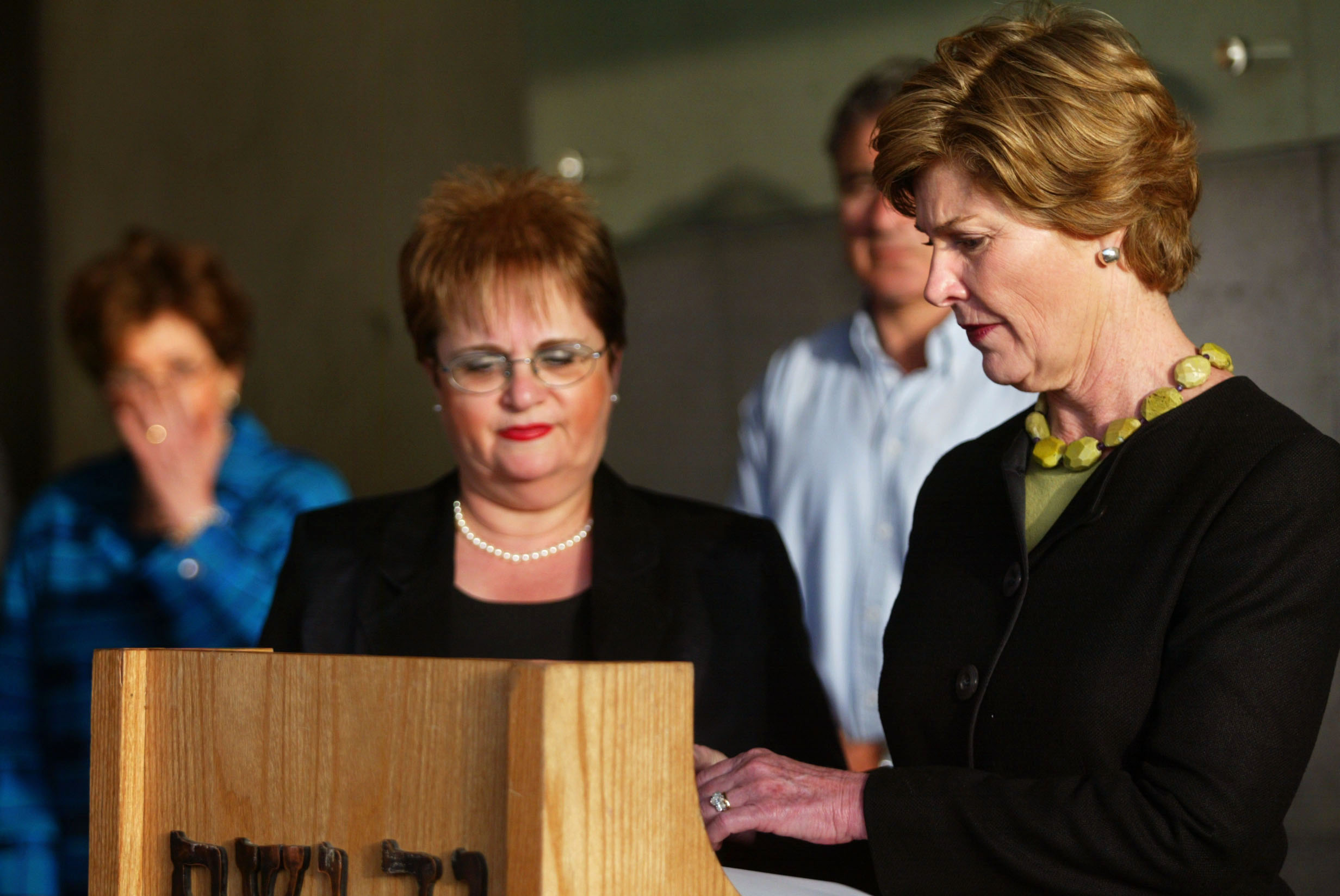 JERUSALEM - MAY 22:  (ISRAEL OUT)  U.S. first lady Laura Bush (R) signs the guestbook at the end of her visit to the Yad Vashem Holocaust Memorial with Gila Katzav (C), wife of Israeli president Moshe Katzav, May 22, 2005 in Jerusalem, Israel. Laura Bush is on a two-day visit to Israel and the Palestinian territories as part of her Middle East tour.  (Photo by Uriel Sinai/Getty Images)