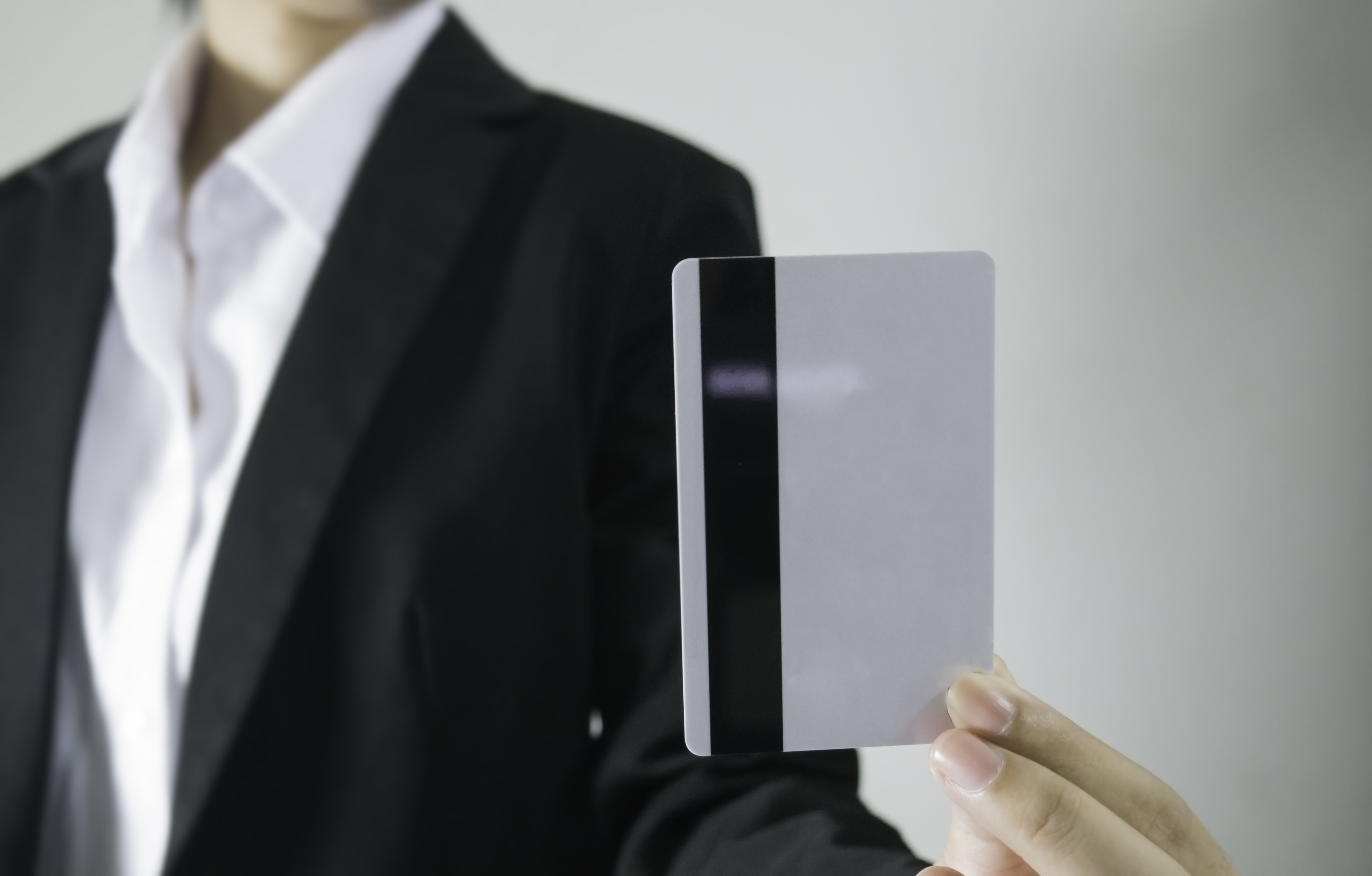 black suit bussiness women holding credit card on grey background