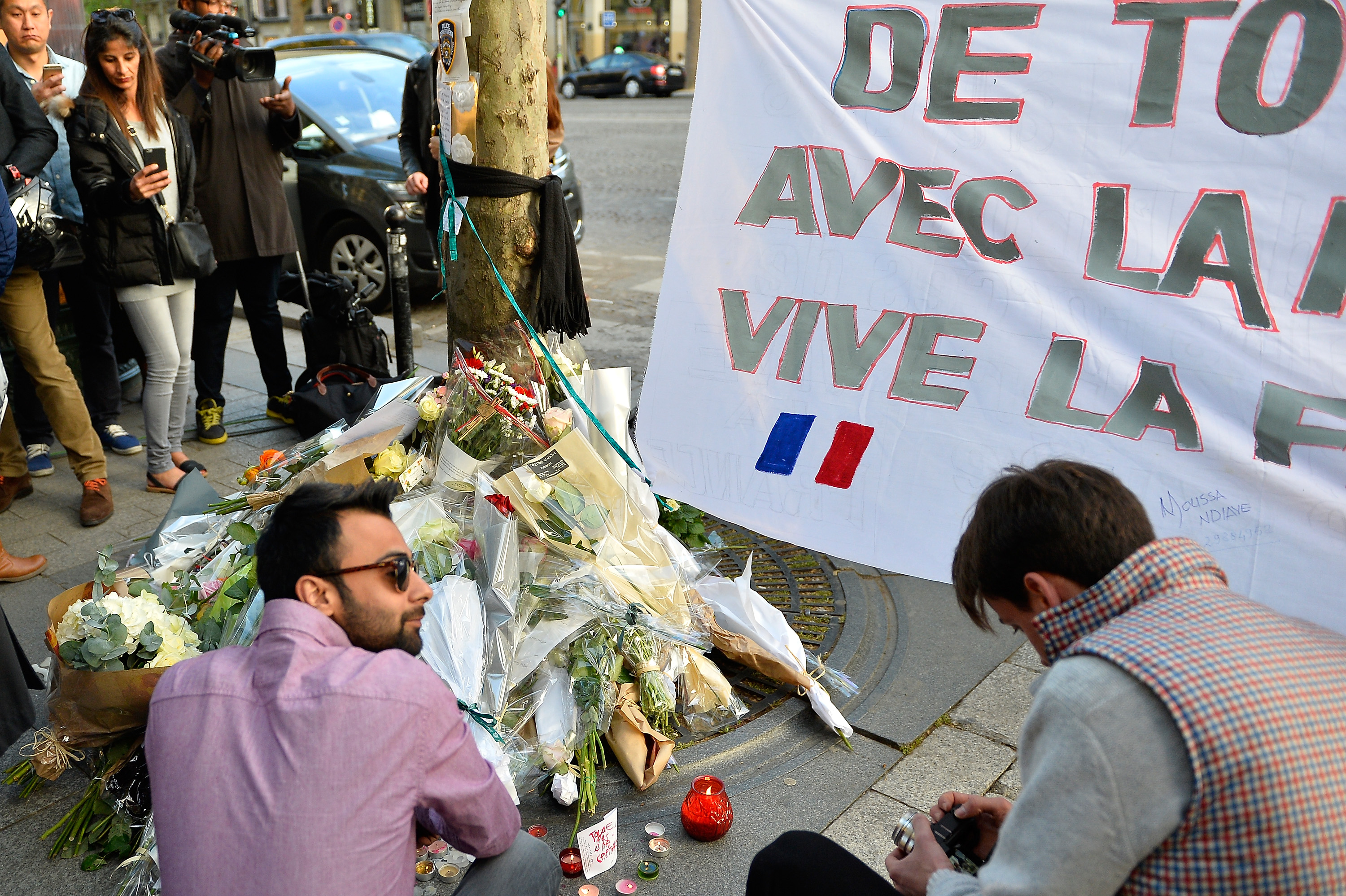 People leave flowers as a tribute to the police officer who lost his life on the Champs-Elysées boulevard in Paris when a gunman opened fire on police officers, one day after the attack, on April 21, 2017.
