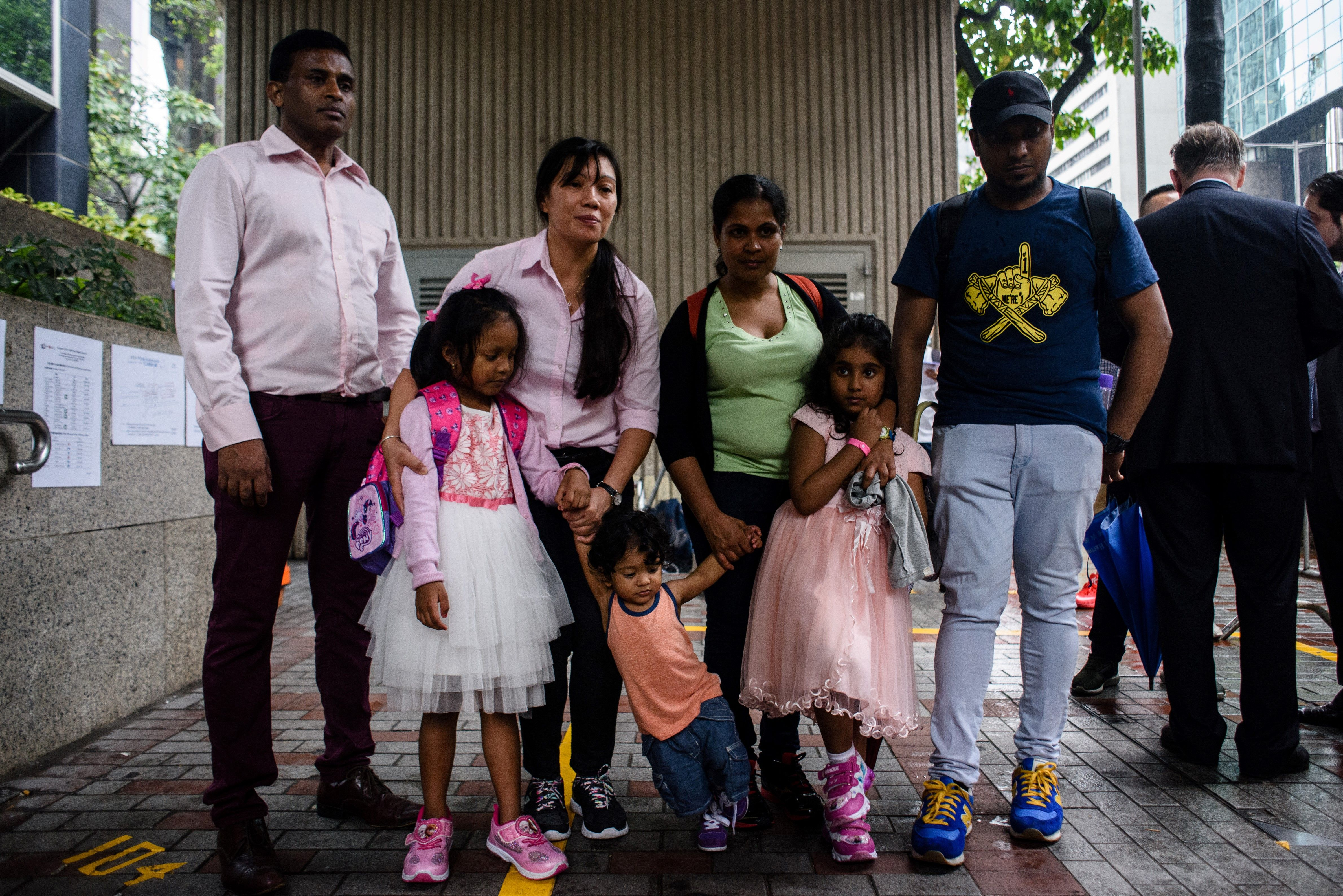 Sri Lankan refugee Ajith Puspa (back L), Filipino refugee Vanessa Rodel (back 2nd L), her daughter Keana (front L), Sri Lankan refugee Nadeeka (back 3rd L), her partner Supun Thilina Kellapatha and their children, son Danath (front C) and daughter Sethumdi (front R), outside the Immigration Tower in Hong Kong, May 15, 2017.