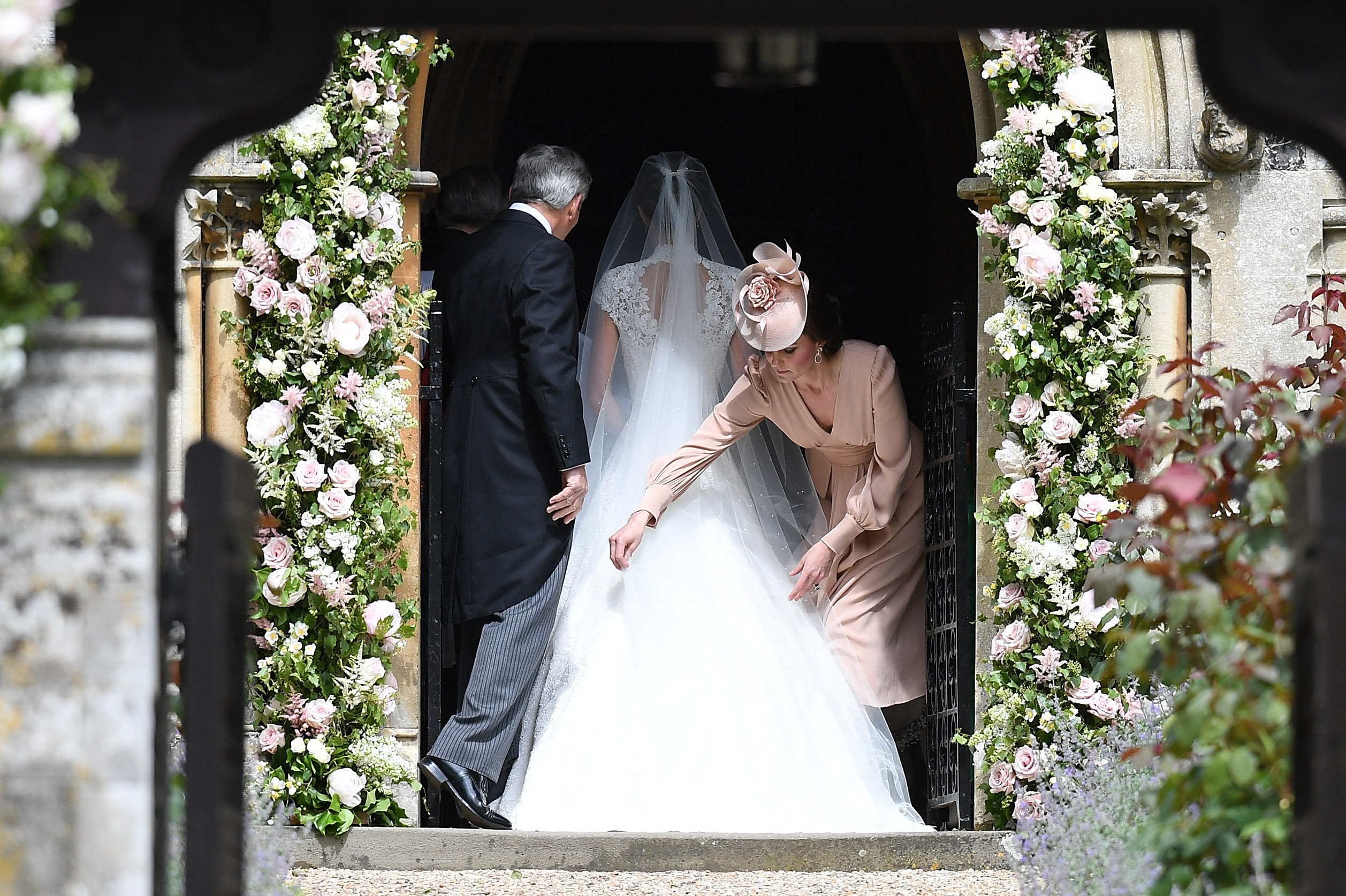Catherine, Duchess of Cambridge adjusts the dress of Pippa Middleton as she enters the church during the wedding of Pippa Middleton and James Matthews at St Mark's Church on May 20, 2017 in Englefield Green, England.