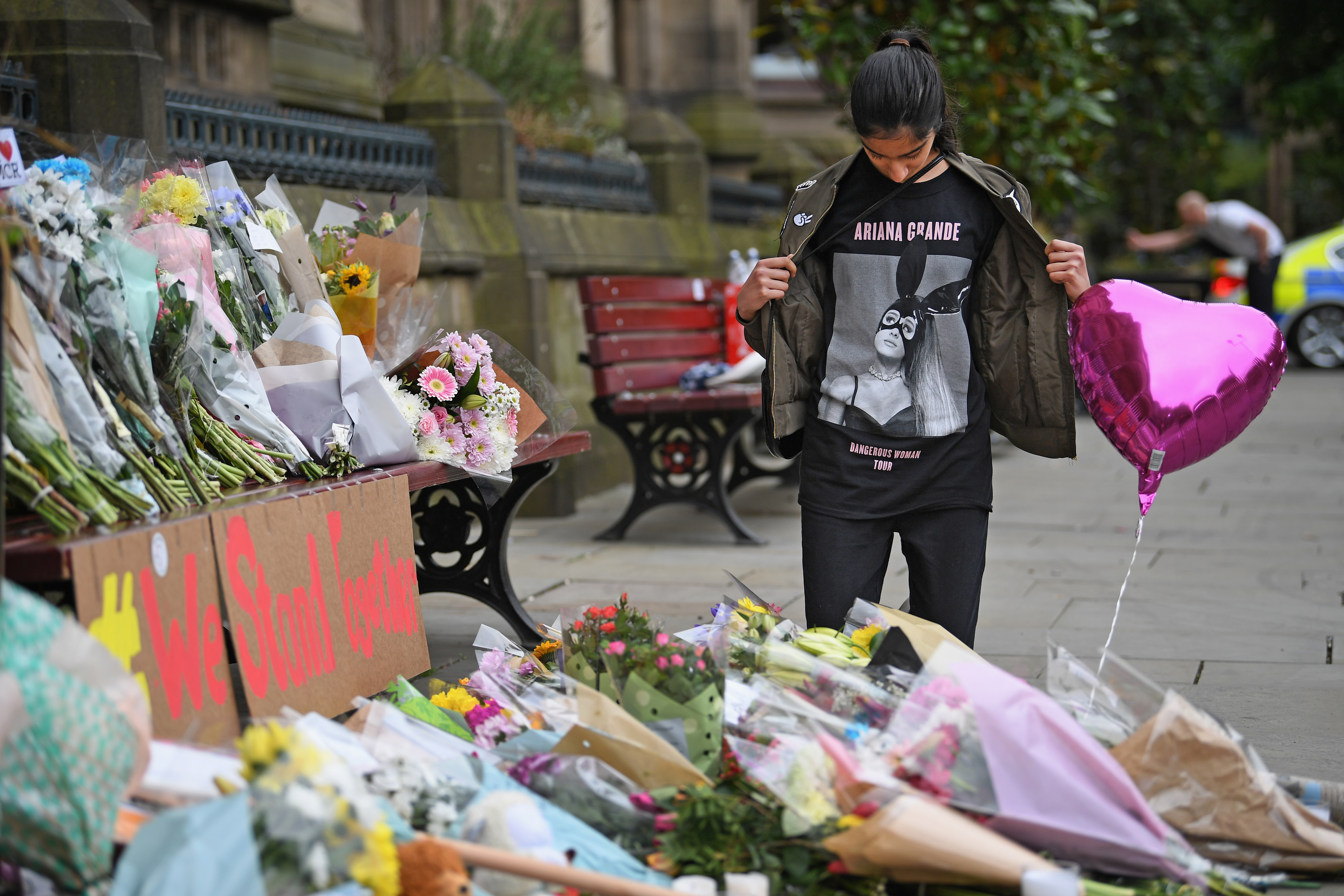 Thirteen year old Iqra Saied, who attended the Ariana Grande concert                        looks at floral tributes and messages as the working day begins on May 24, 2017 in Manchester, England.