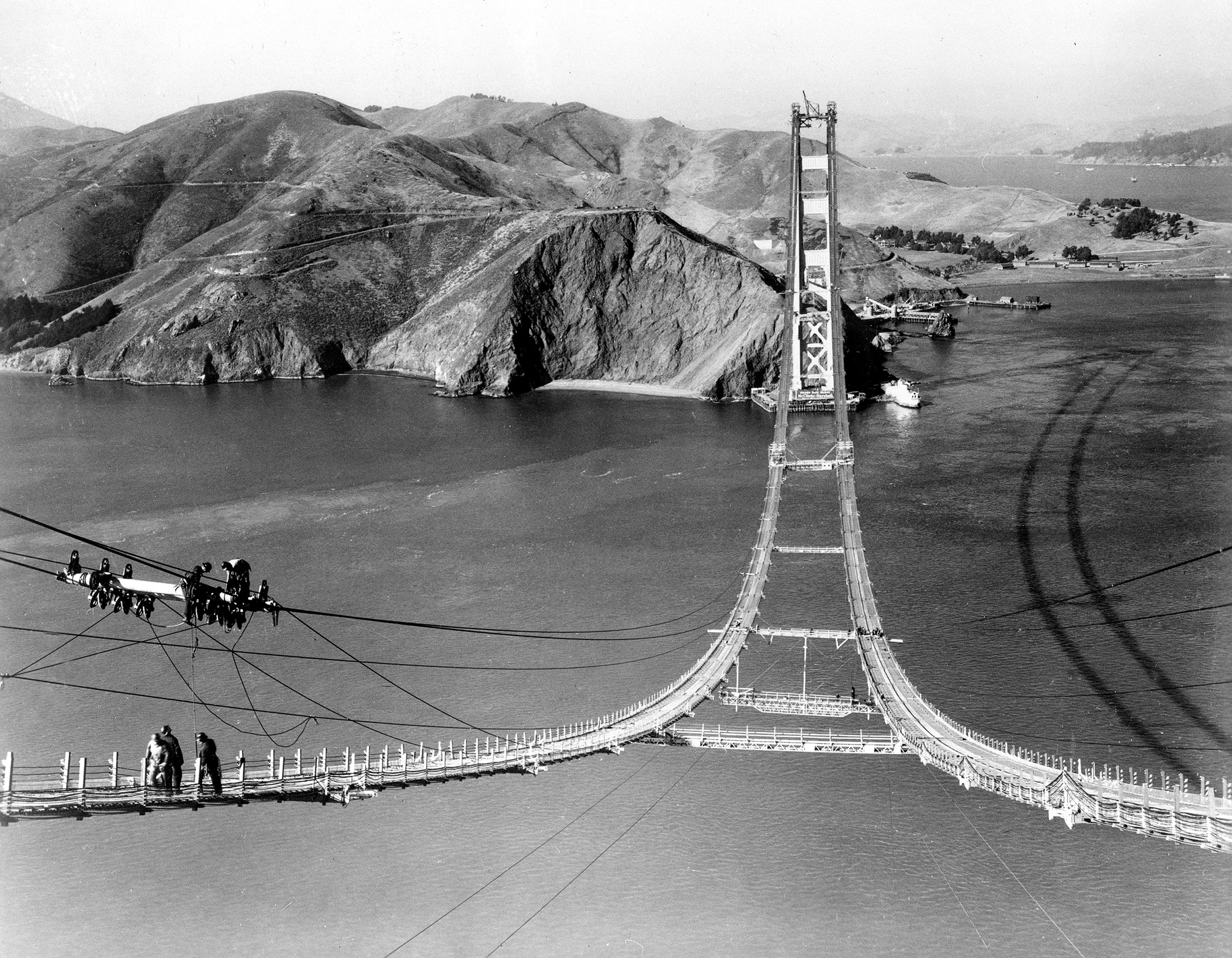 Workers complete the catwalks for the Golden Gate Bridge, spanning the Golden Gate Strait, prior to spinning the bridge cables during construction in San Francisco, Ca., Oct. 25, 1935.