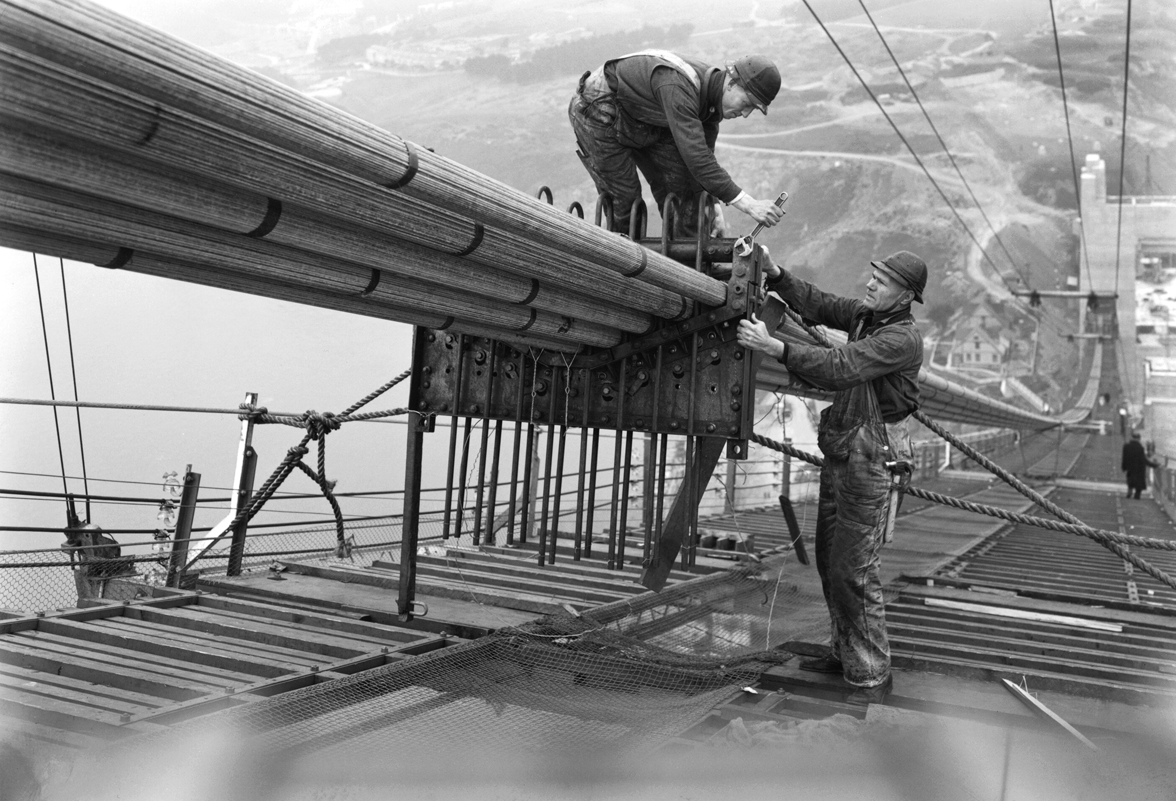 Workers on the catwalks bundling the cables during the construction of the cables of the Golden Gate Bridge, San Francisco, California, circa 1936.