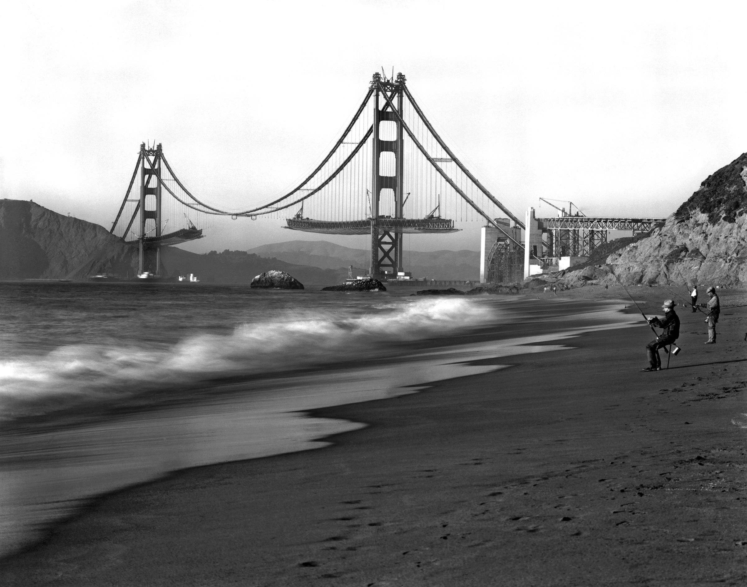 Fishermen on Baker Beach enjoy the view of the Golden Gate Bridge under construction, San Francisco, California, 1930s.
