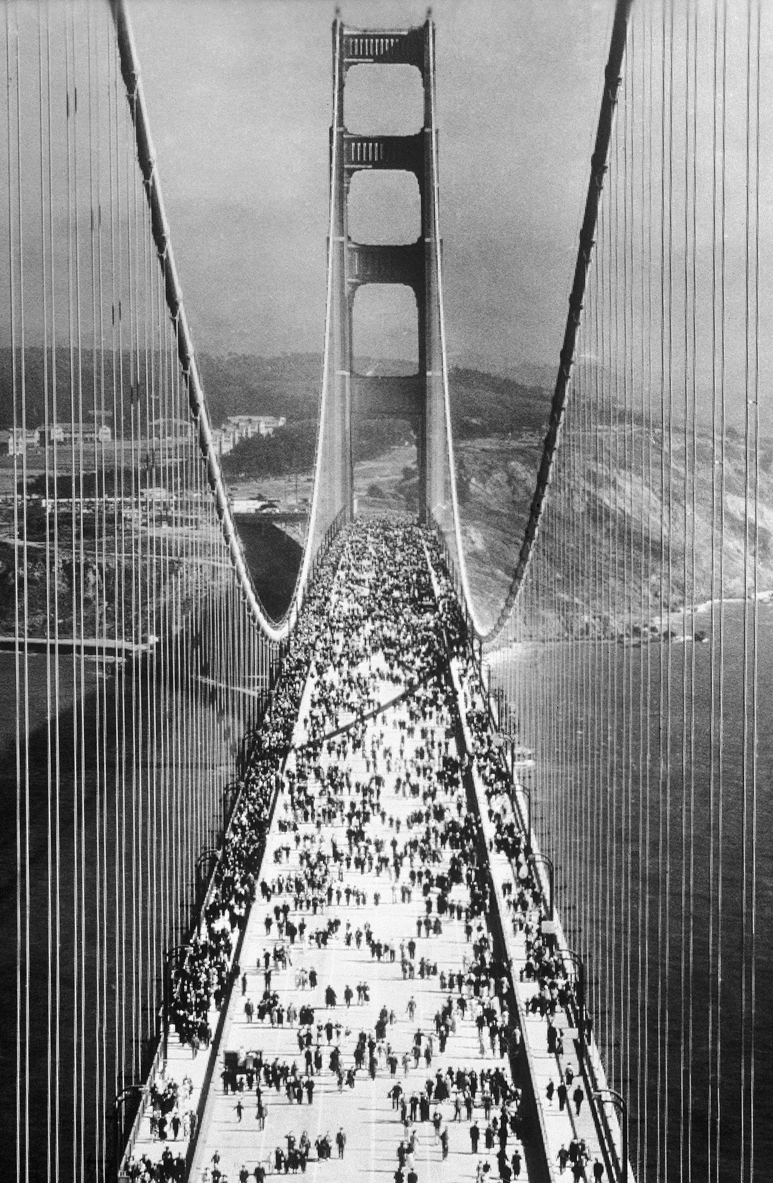 A view taken from one of the towers of the Golden Gate Bridge of pedestrians swarming across  immediately after the opening on May 27, 1937.
